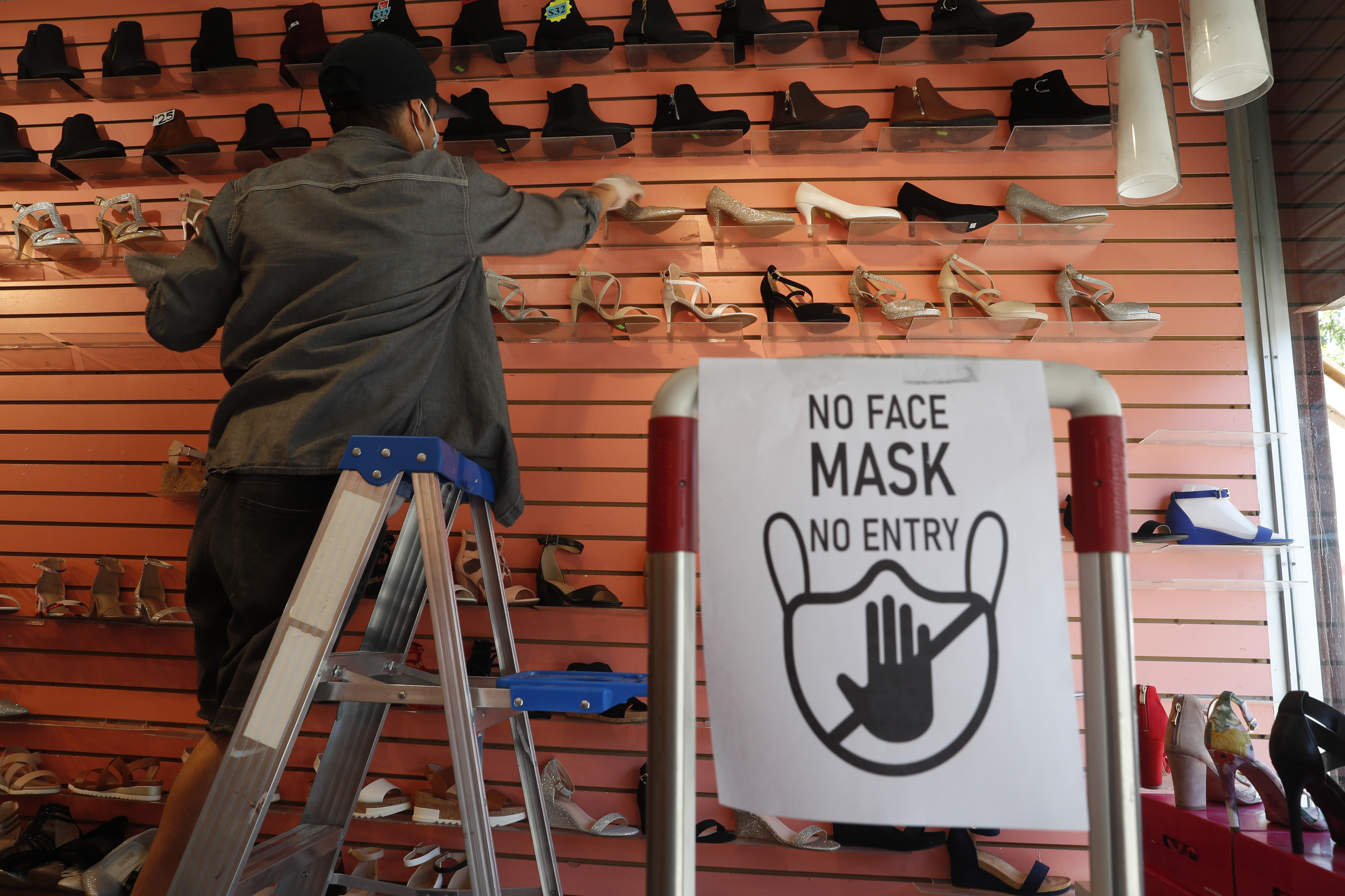 Manager Angel Ramos arranges shoes on a display in Top shoes, June 8, 2020, in the Brooklyn borough of New York, after retail stores were allowed to reopen to customers on the first day marking Phase 1 reopening for New York City.