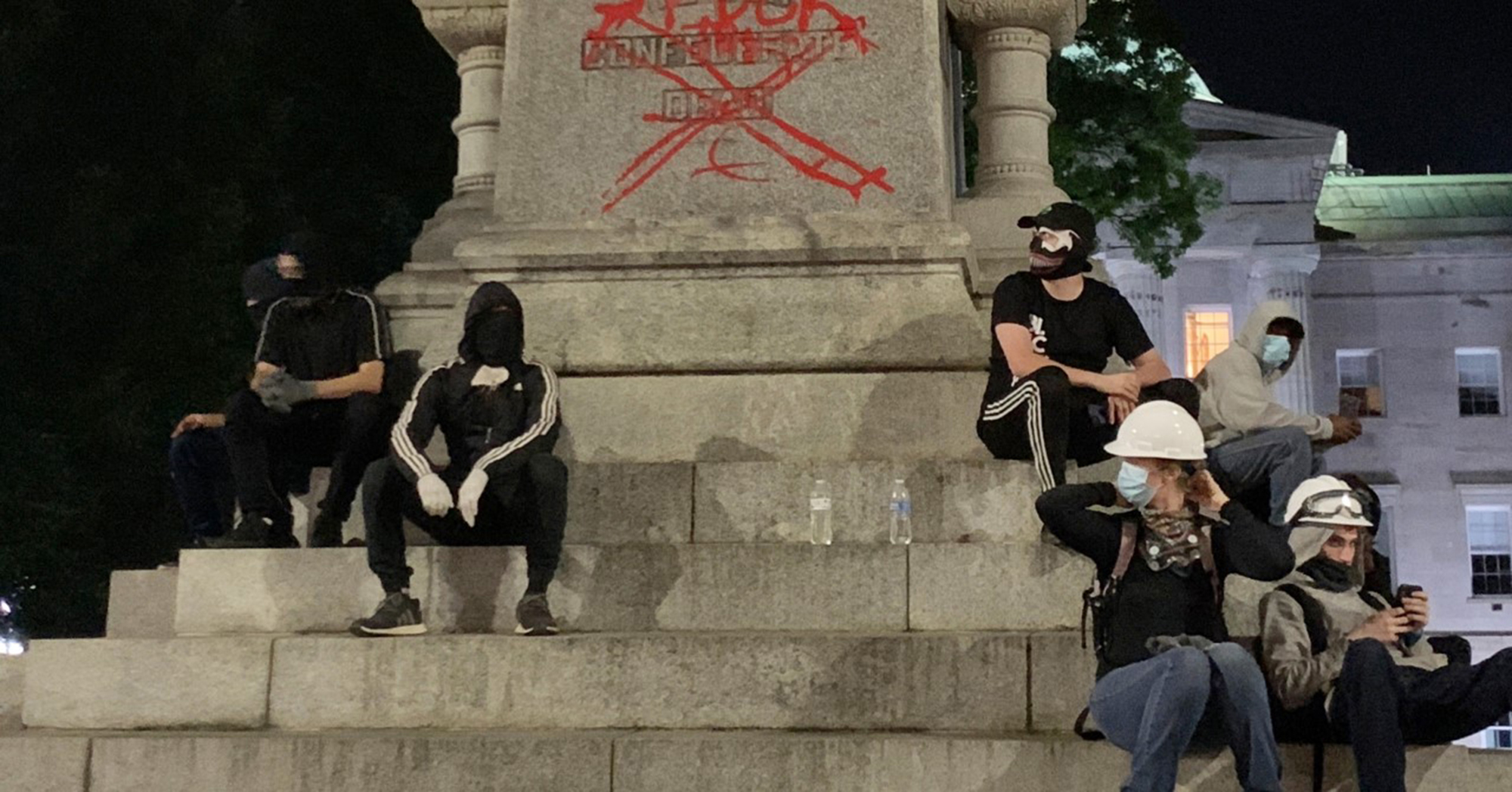 A group of people sit at the base of a confederate statue on the grounds of the State Capitol in Raleigh, N.C., after protesters spray-painted messages, May 31, 2020.