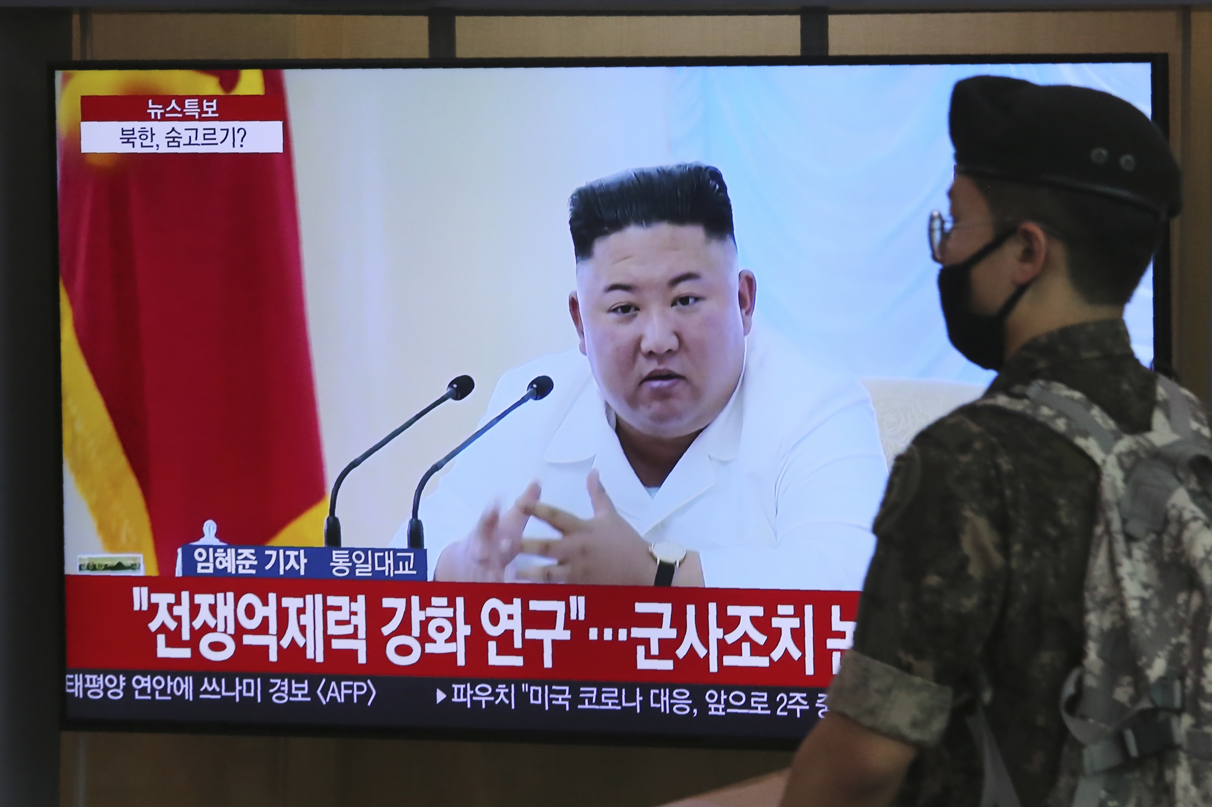 A South Korean army soldier passes by a TV showing a file image of North Korean leader Kim Jong Un during a news program at the Seoul Railway Station in Seoul, South Korea, Wednesday, June 24, 2020. Kim suspended his military's plans to take unspecified retaliatory action against South Korea, state media said Wednesday, possibly slowing a pressure campaign against its rival amid stalled nuclear negotiations with the Trump administration. The Korean letters read:  Strengthening deterrence of war.