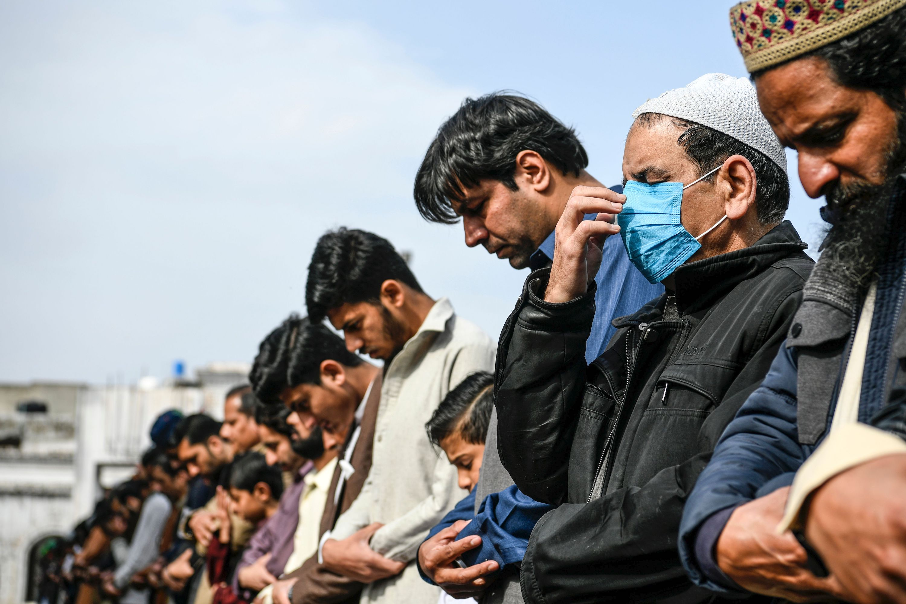 A resident (R) wearing a facemask as a preventive measure against the spread of the COVID-19 coronavirus offers Friday prayers along with other Muslims at a mosque in Rawalpindi on March 13, 2020.