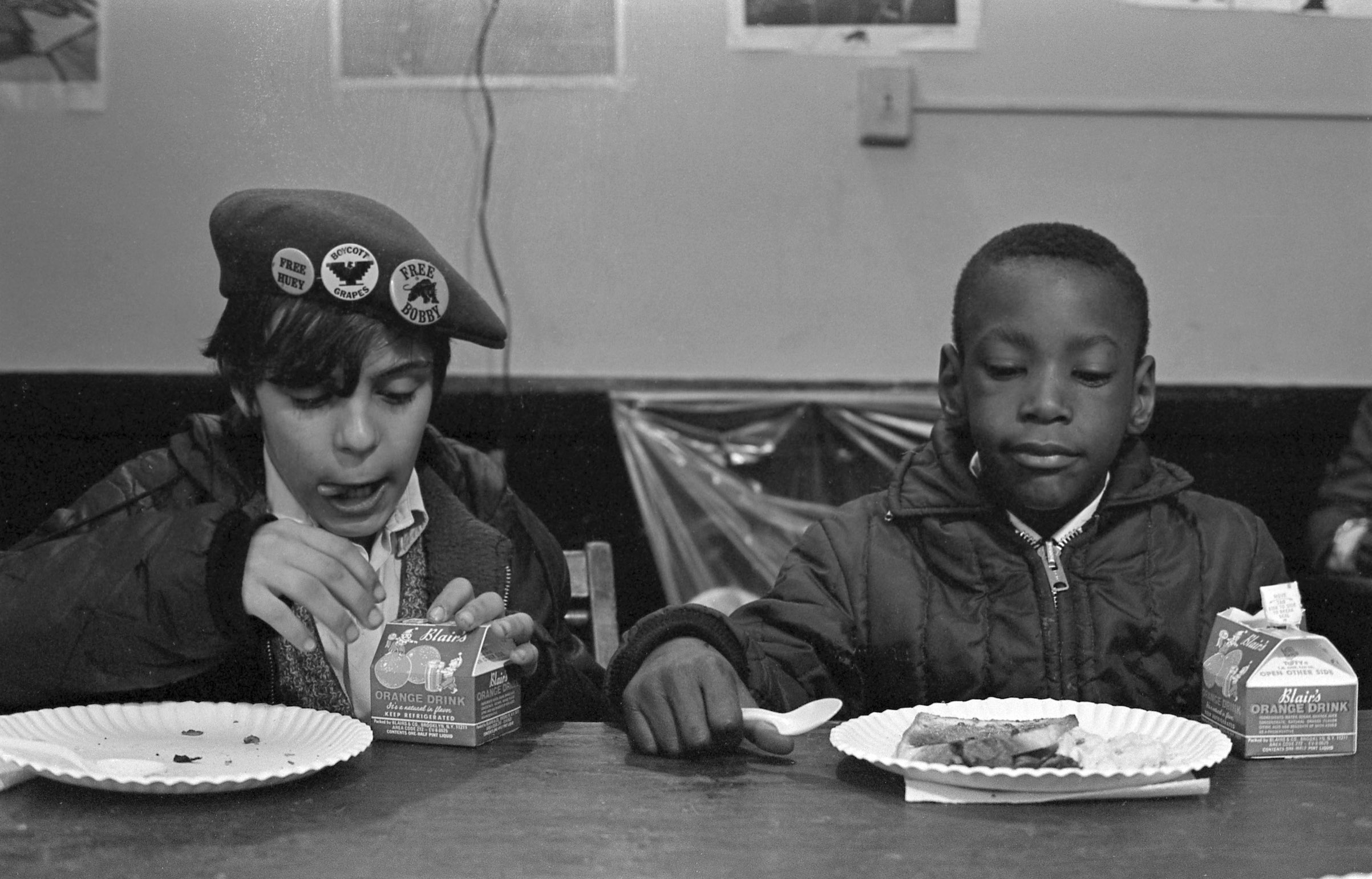 Two young boys eat during a free breakfast for children program sponsored by the Black Panther Party, New York City, winter 1969.