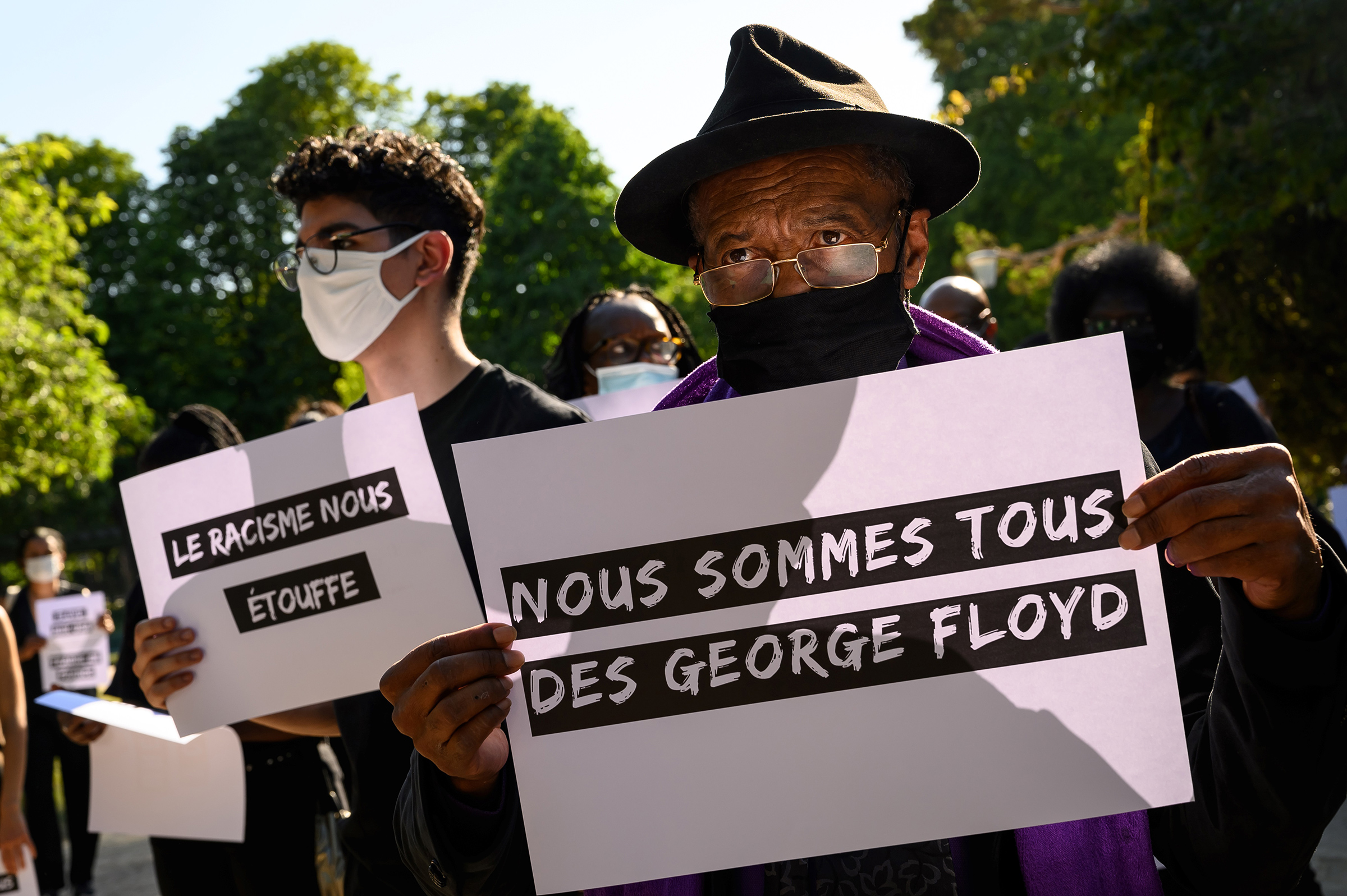 Protesters hold placards reading  We are all George Floyd  (R) and  Racism is suffocating us  (L) during a demonstration outside the United States Embassy in Paris on June 1 after the police killing of unarmed black man George Floyd in the U.S.
