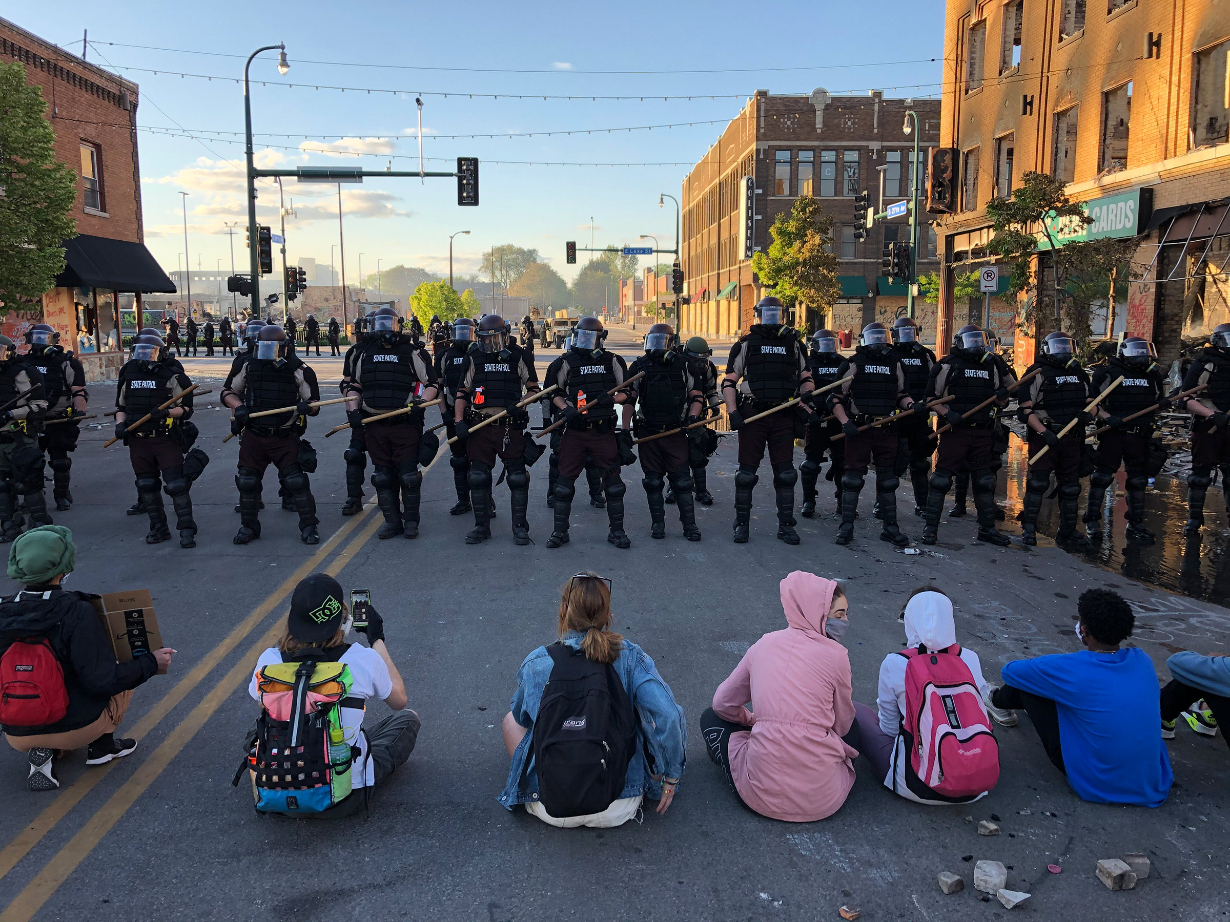 People sit on the street in front of a row of police officers during a rally in Minneapolis on May 29 after the death of George Floyd.