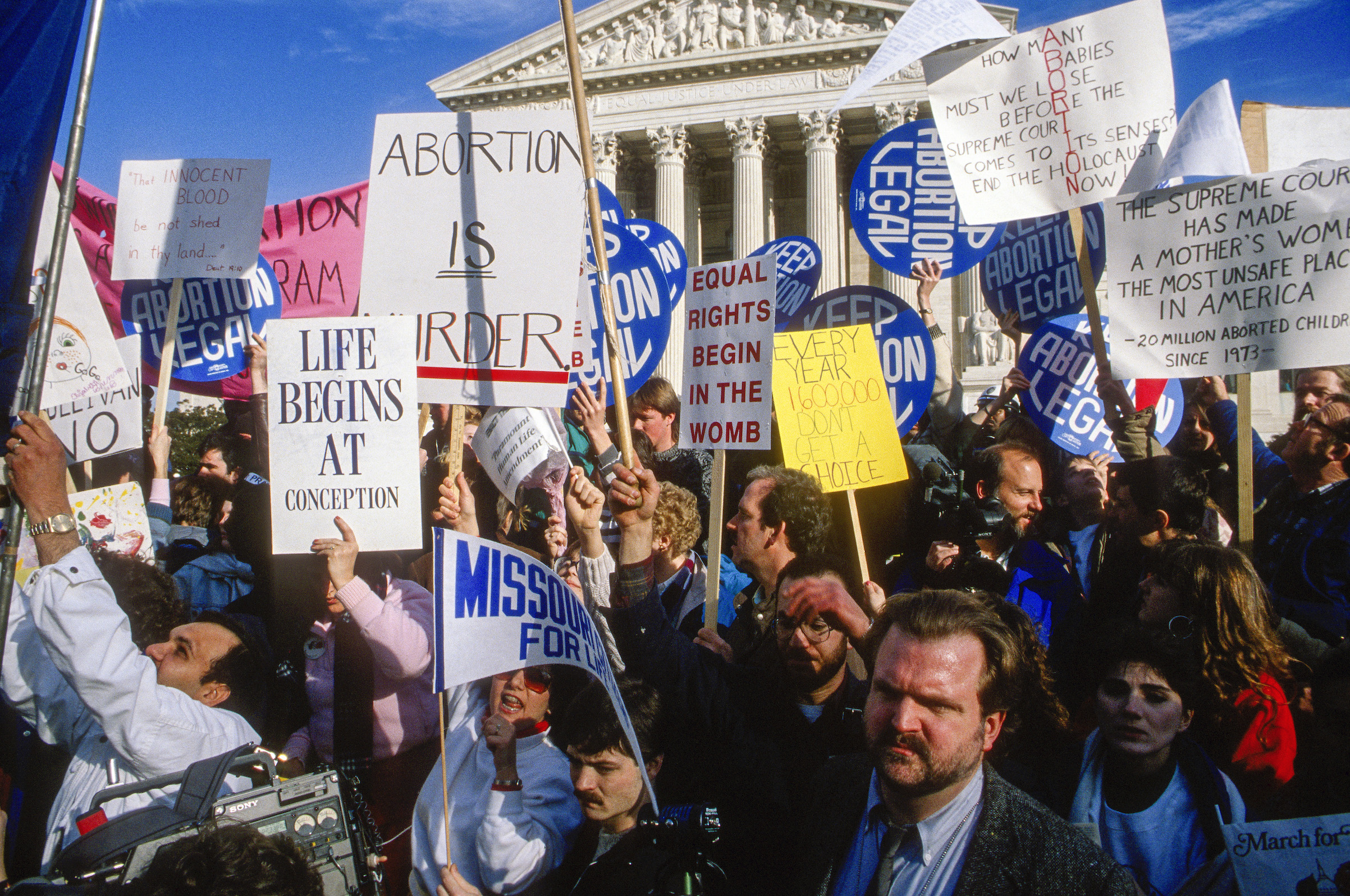 Anti-abortion and abortion-rights demonstrators both wave their signs outside the United States Supreme Court Building in Washington, D.C., on Jan. 22, 1989.