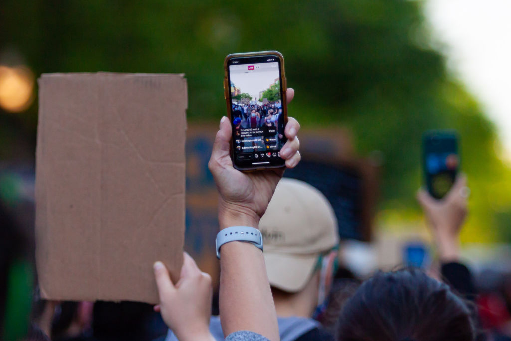 Demonstrators live-stream the protest via smartphones in Uptown neighborhood of Chicago, the United States, June 1, 2020.
