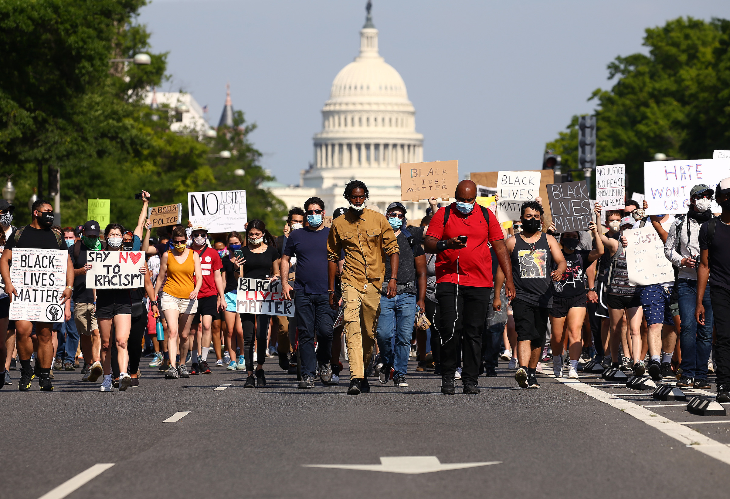Demonstrators march down Pennsylvania Avenue near the Trump International Hotel during a protest against police brutality and the death of George Floyd, on June 3, 2020 in Washington, D.C.