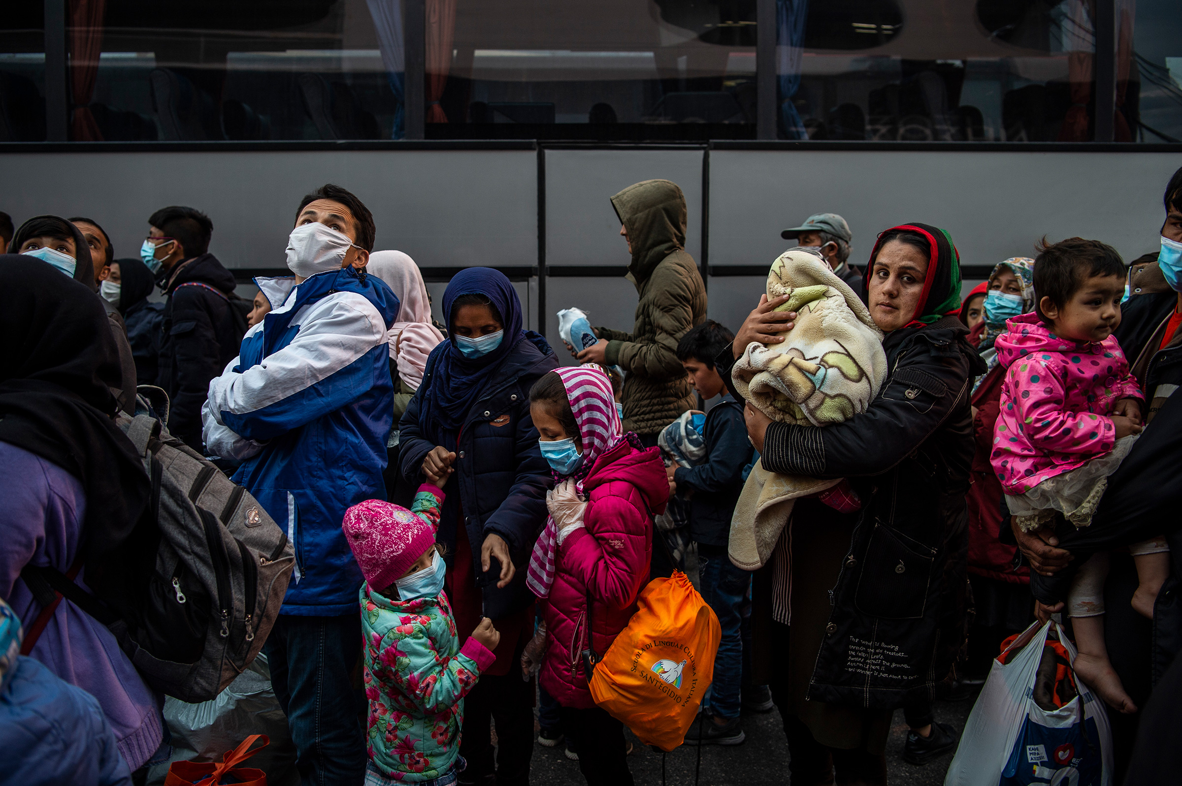 Migrants from Moria refugee camp arriving by ship from the island of Lesbos, stand in the port of Piraeus near Athens on May 4, 2020.