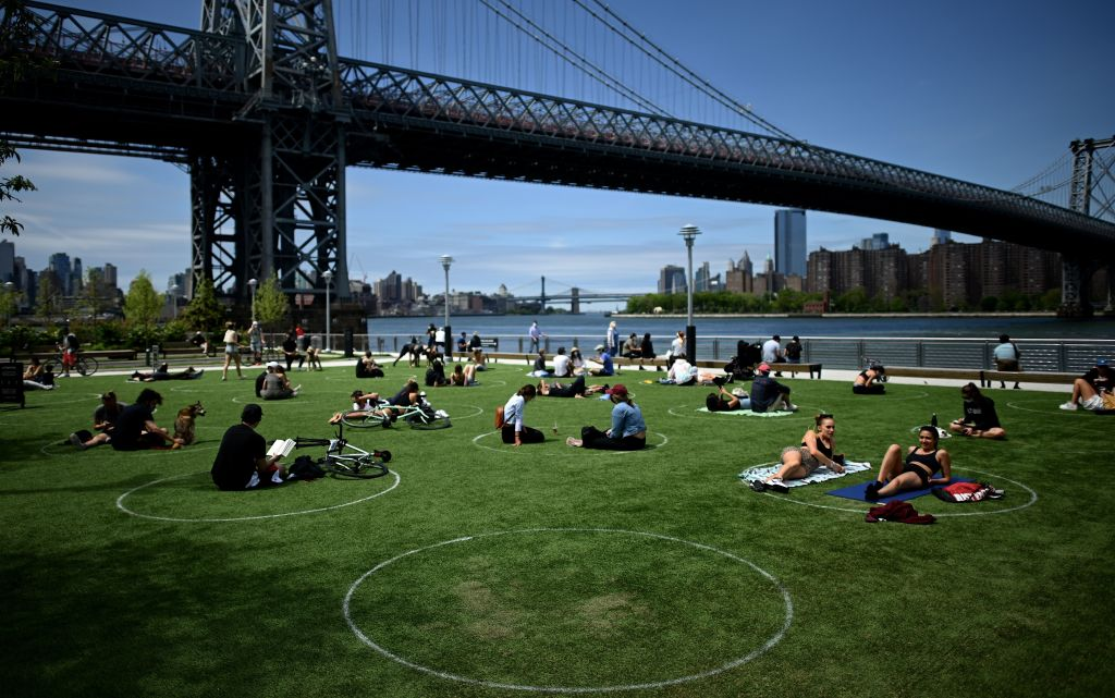 People are seen practicing social distancing in white circles in Domino Park in Williamsburg, Brooklyn, during the Covid-19 pandemic on May 17, 2020.
