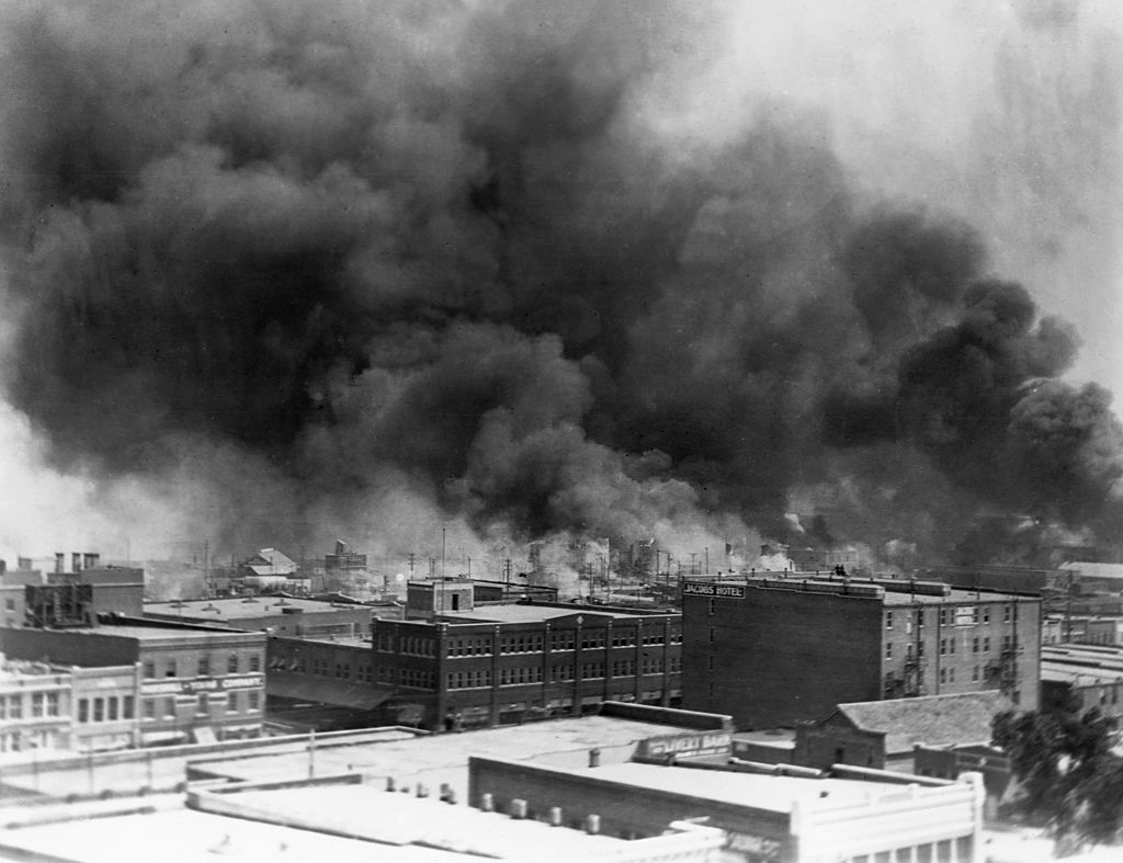 Black smoke billows from fires during the Tulsa Race Massacre of 1921, in the Greenwood District of Tulsa, Oklahoma.