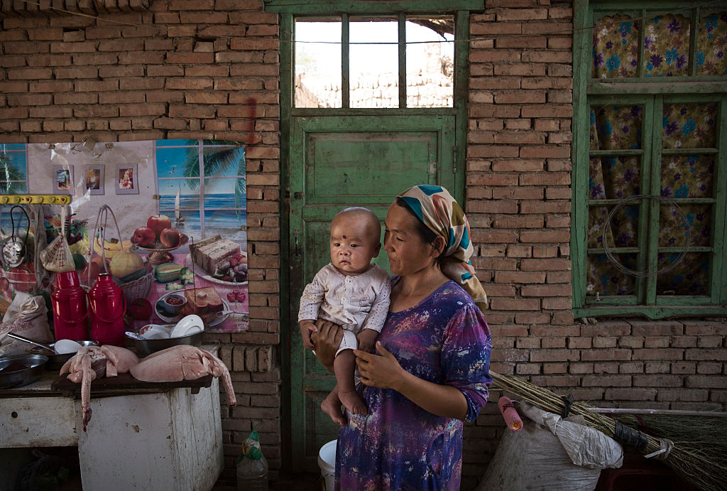 A Uighur woman holds a child in her home as they prepare food in Turpan County, in the far western Xinjiang province, China on Sept. 12, 2016.