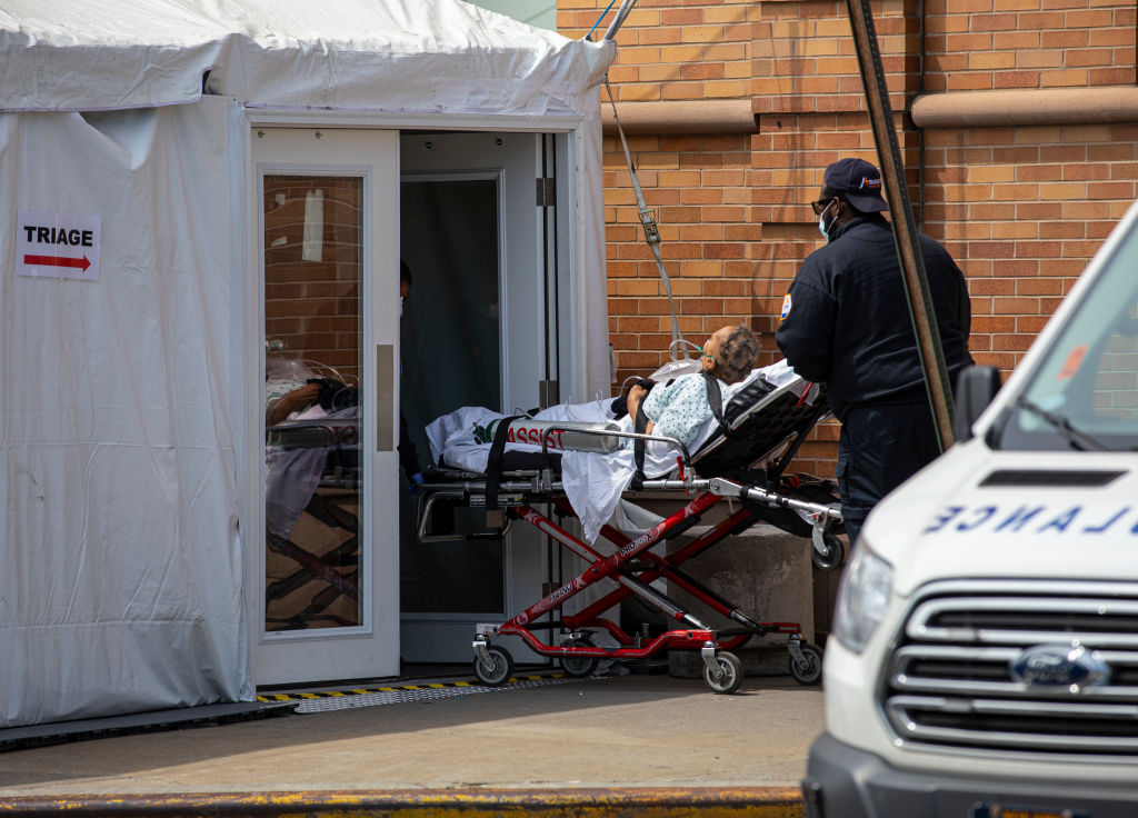 A private ambulance team brings in a probable COVID-19 patient to a triage room outside the Maimonides Medical Center in New York City on April 7, 2020.