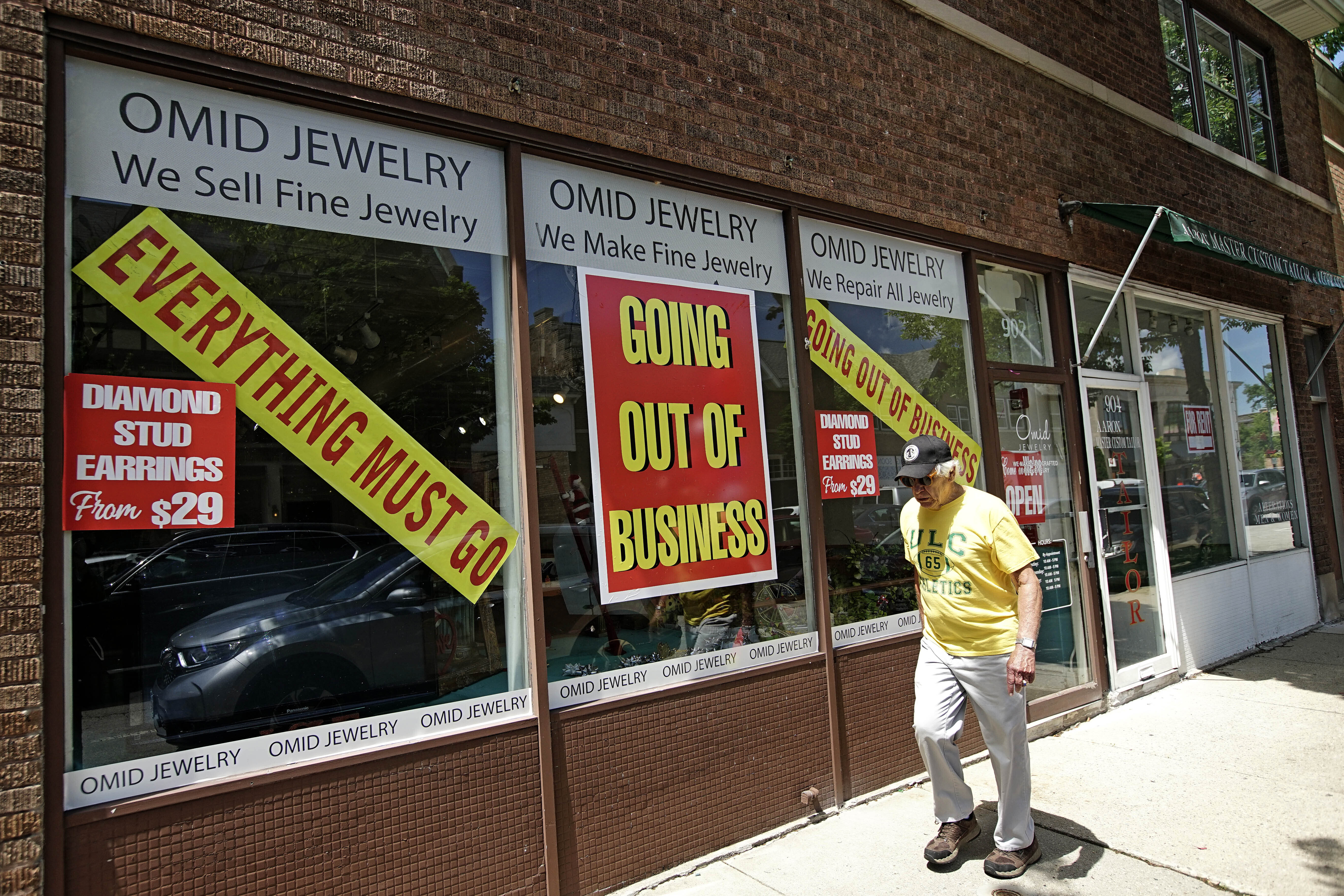 A man walks past a retail store that is going out of business due to the coronavirus pandemic in Winnetka, Ill., June 23, 2020.