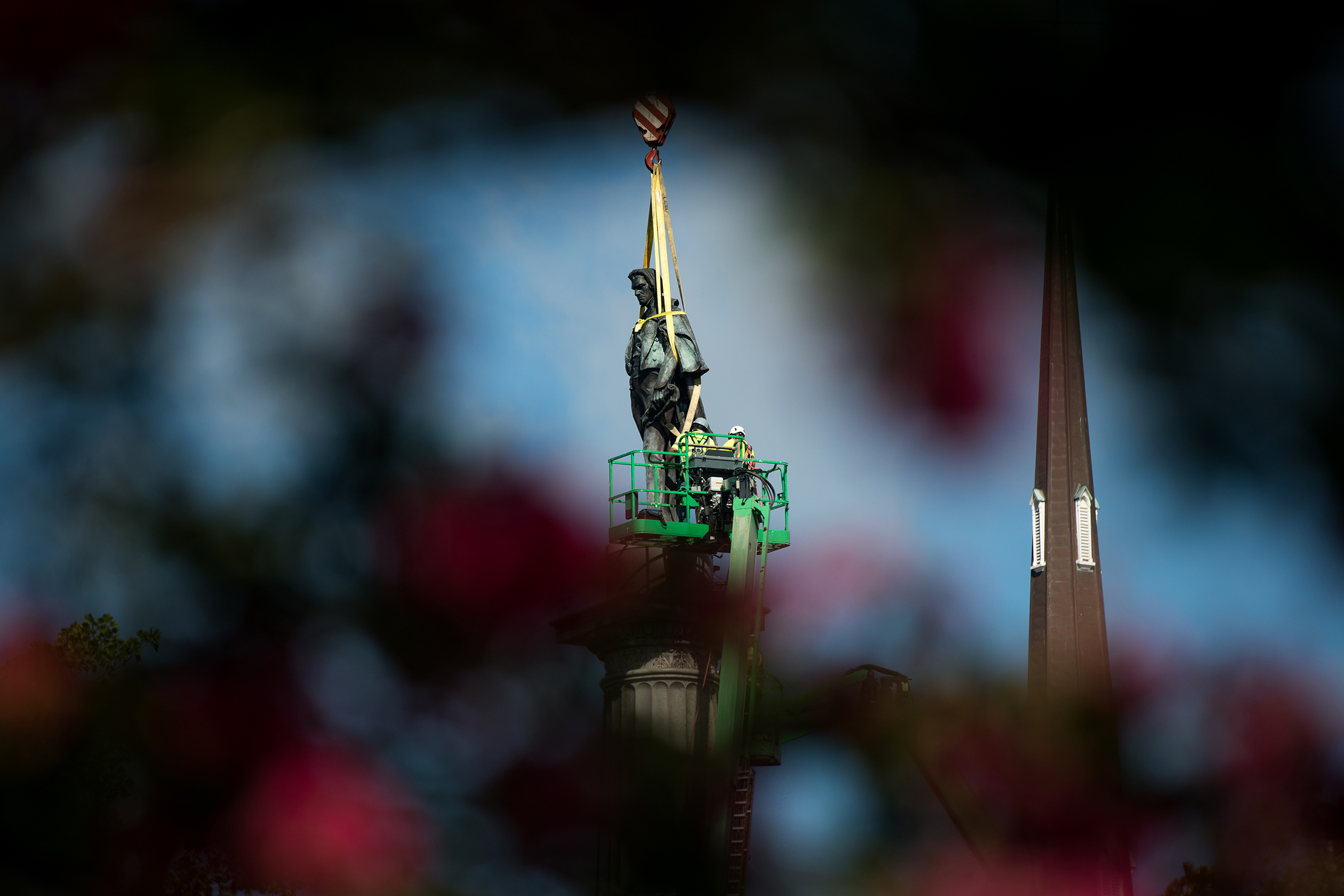 Workers dismantle the John C. Calhoun statue atop a monument in Marion Square in Charleston, S.C., on June 24, 2020.