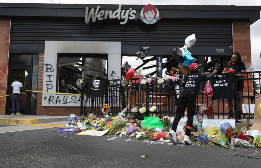 People visit the memorial dedicated to Rayshard Brooks in front of the Wendy's restaurant on June 16, 2020 in Atlanta, Georgia.