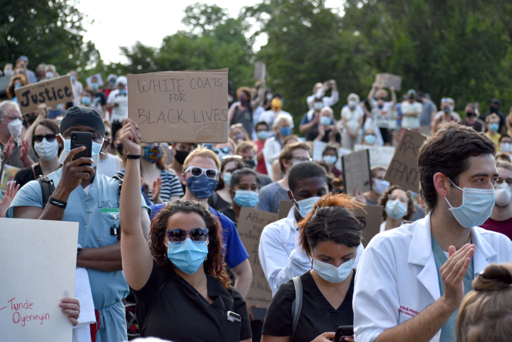 Medical workers in face masks hold signs during a rally organized by a group called White Coats for Black Lives in New York City on May 25, 2020.