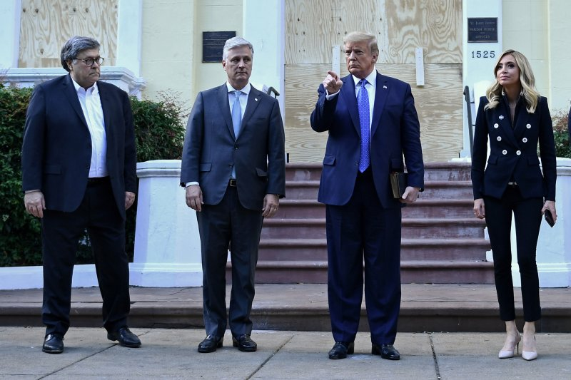 US President Donald Trump holds up a Bible as he gestures, alongside US Attorney General William Barr (L), White House national security adviser Robert O'Brien (2nd-L) and White House press secretary Kayleigh McEnany, outside of St John's Episcopal church across Lafayette Park in Washington, D.C., on June 1, 2020.