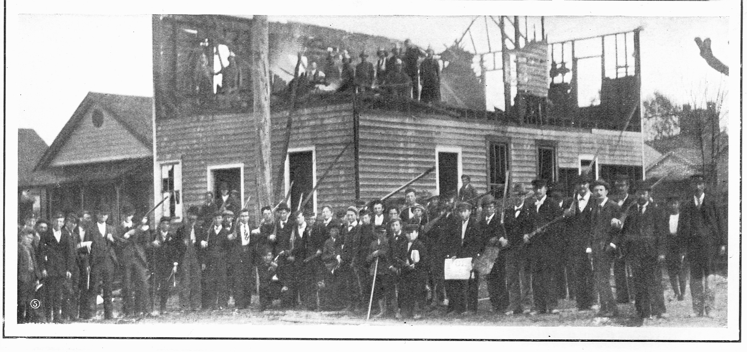 Men gather outside the charred remains of The Daily Record after the 1898  race riots in Wilmington, North Carolina.