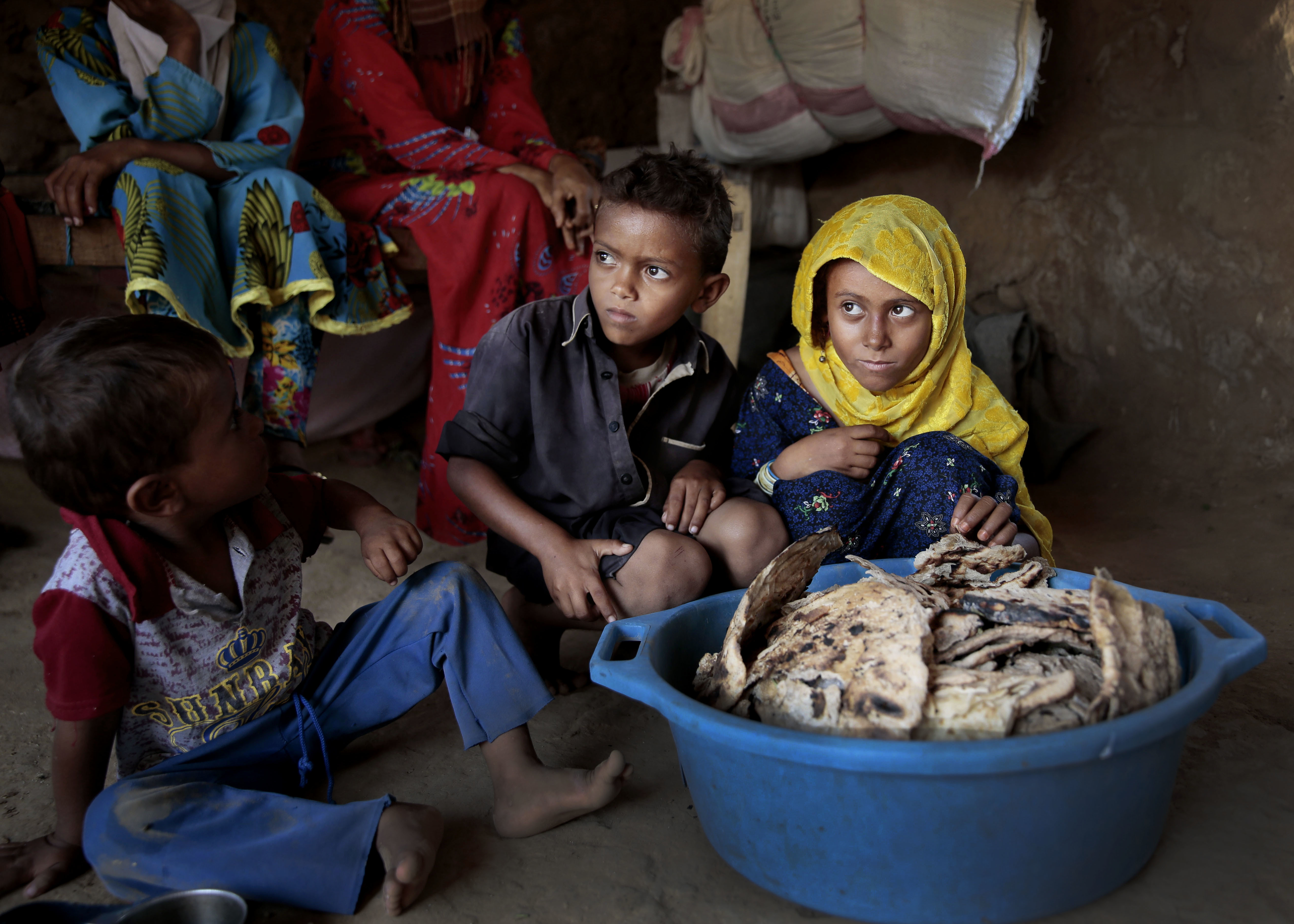 Children sit in front of moldy bread in their shelter, in Aslam, Hajjah, Yemen on Oct. 1, 2018.
