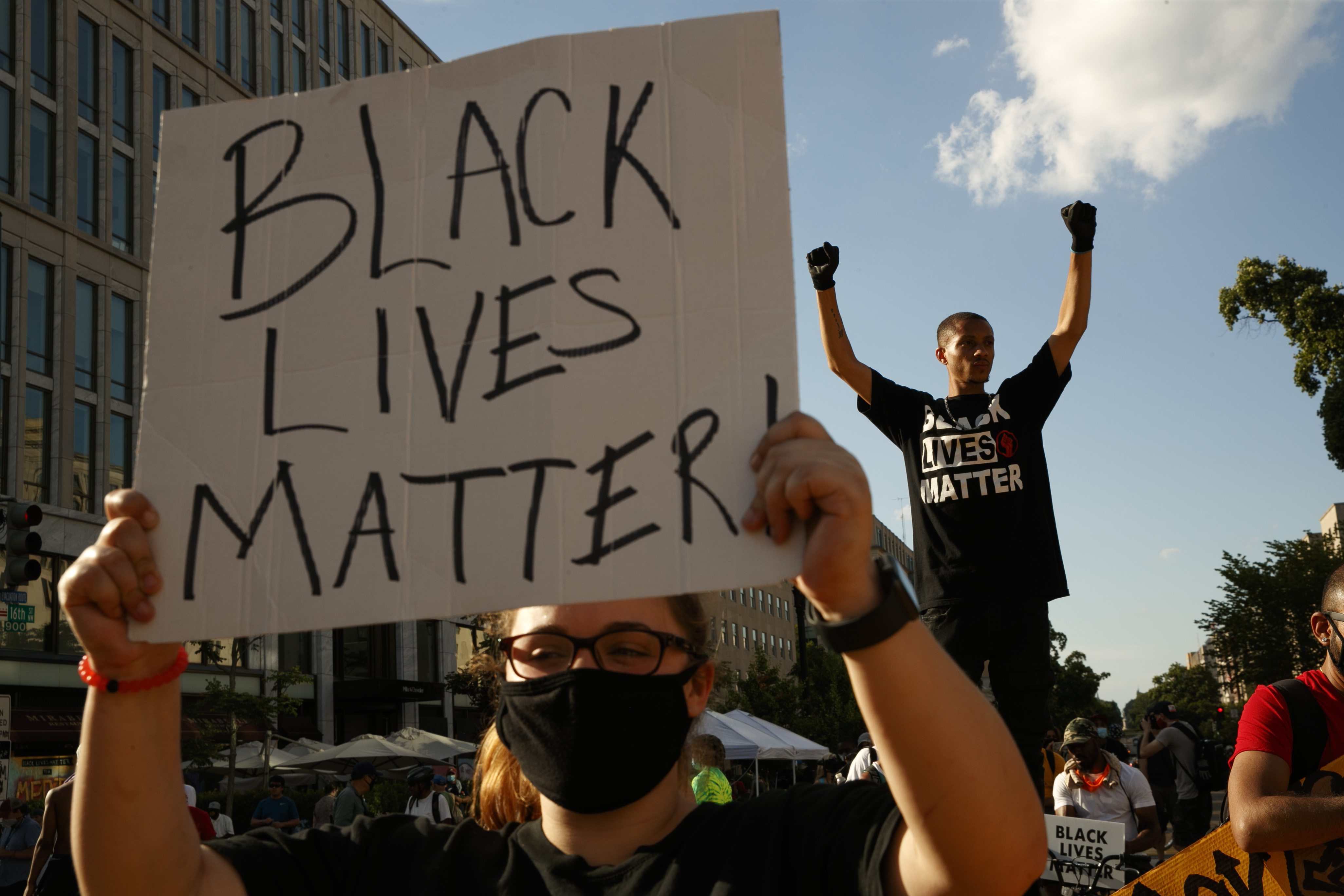 In this June 24, 2020, file photo, Antonio Mingo, right, holds his fists in the air as demonstrators protest in front of a police line on a section of 16th Street that's been renamed Black Lives Matter Plaza, in Washington.