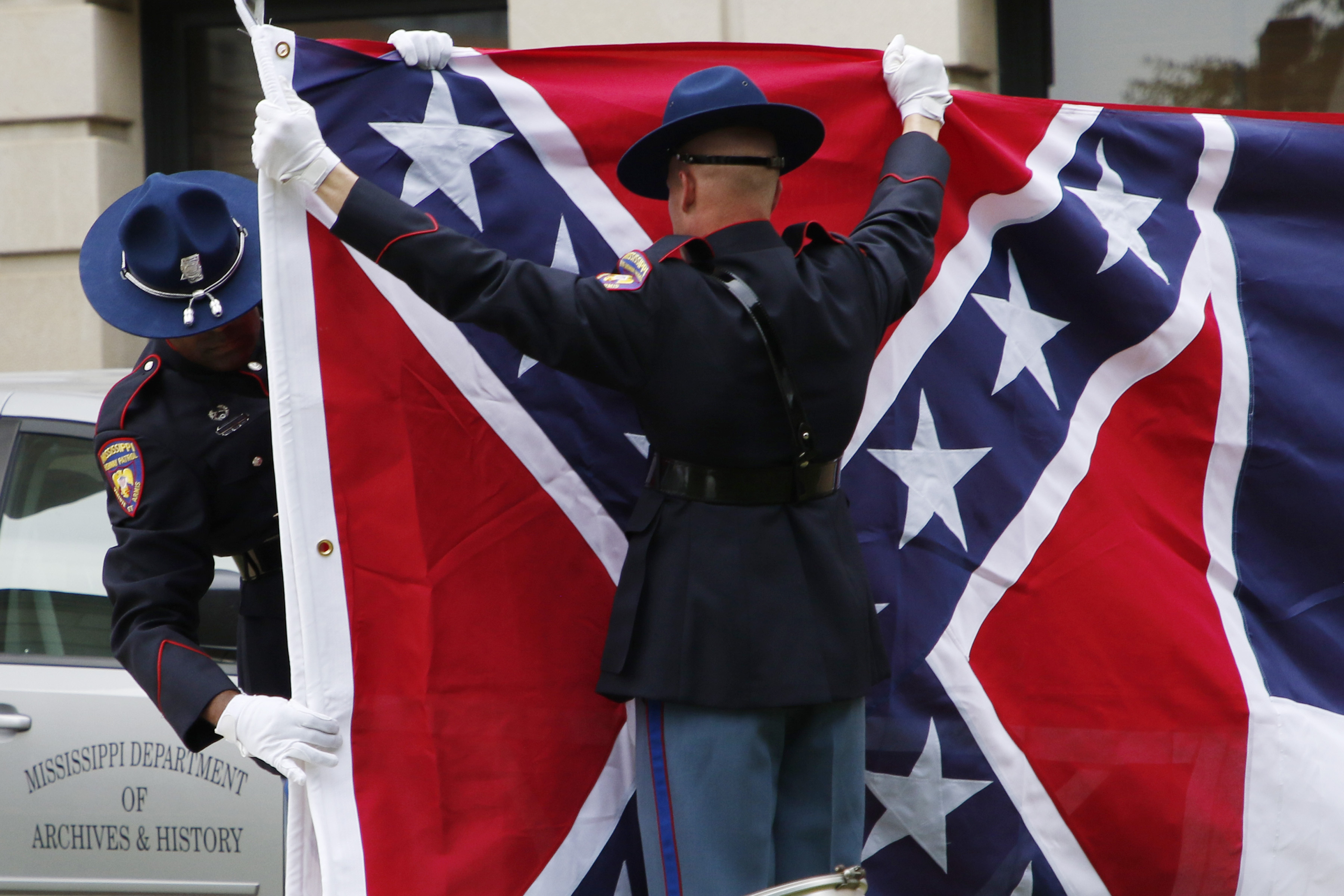 A Mississippi Highway Safety Patrol honor guard carefully folds the retired Mississippi state flag after it was raised over the Capitol grounds one final time in Jackson, Miss., Wednesday, July 1, 2020.