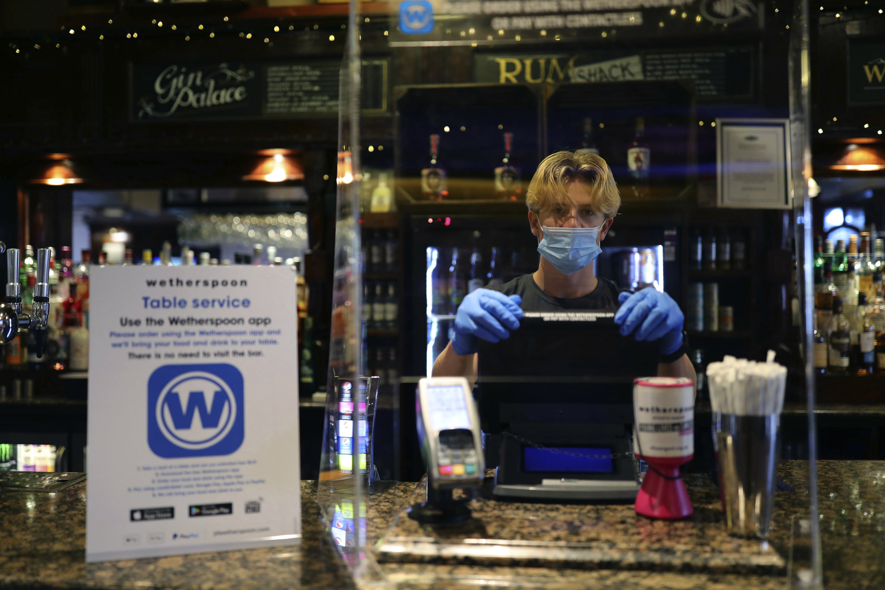 A member of staff wearing PPE, stands behind a screen as he waits to serve drinkers at the reopening The Toll Gate, a Wetherspoons pub in Hornsey, north London, as coronavirus lockdown restrictions are eased across the country, Saturday July 4, 2020.