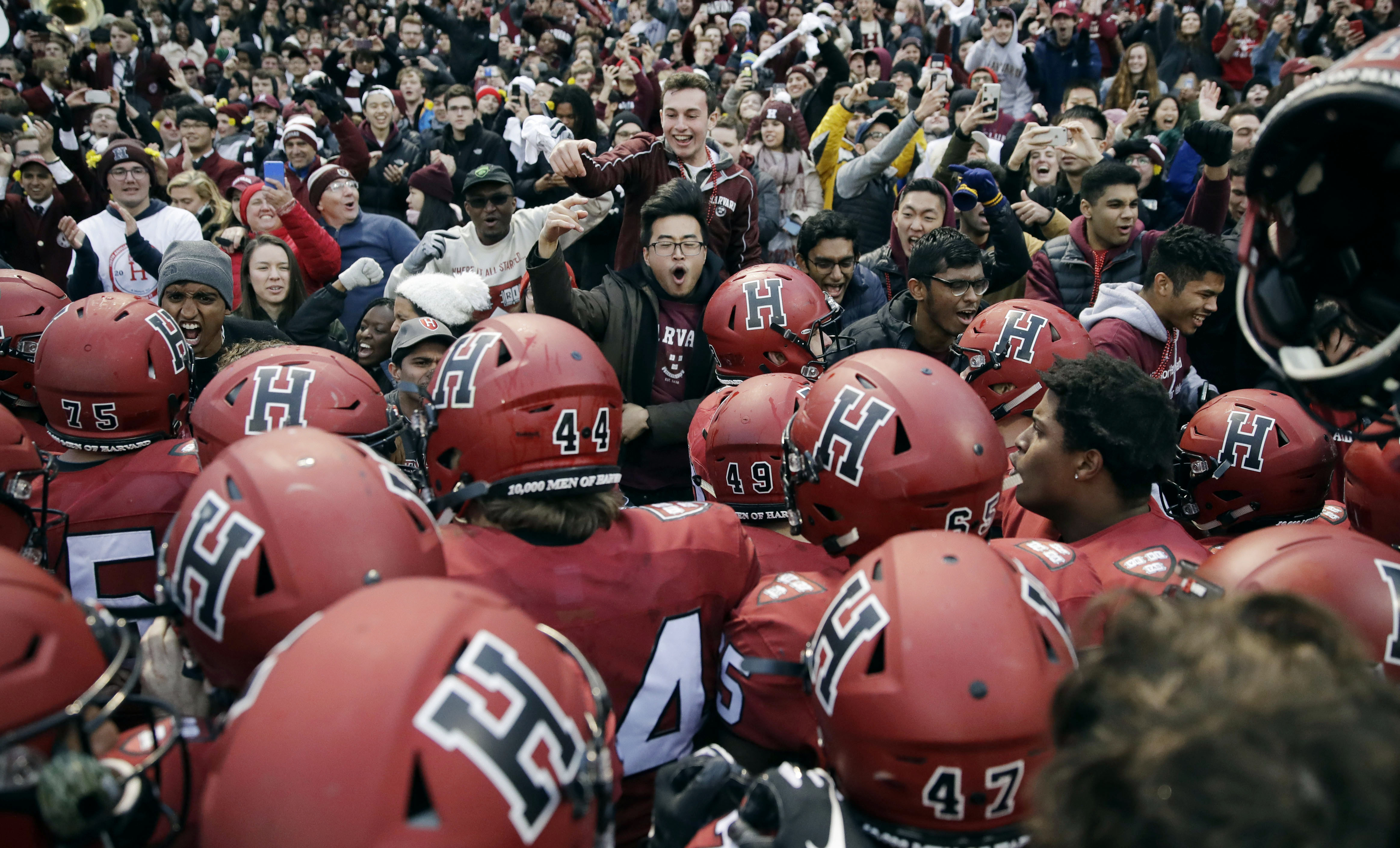 Harvard players, students and fans celebrate their 45-27 win over Yale after an NCAA college football game at Fenway Park in Boston on Nov. 17, 2018.