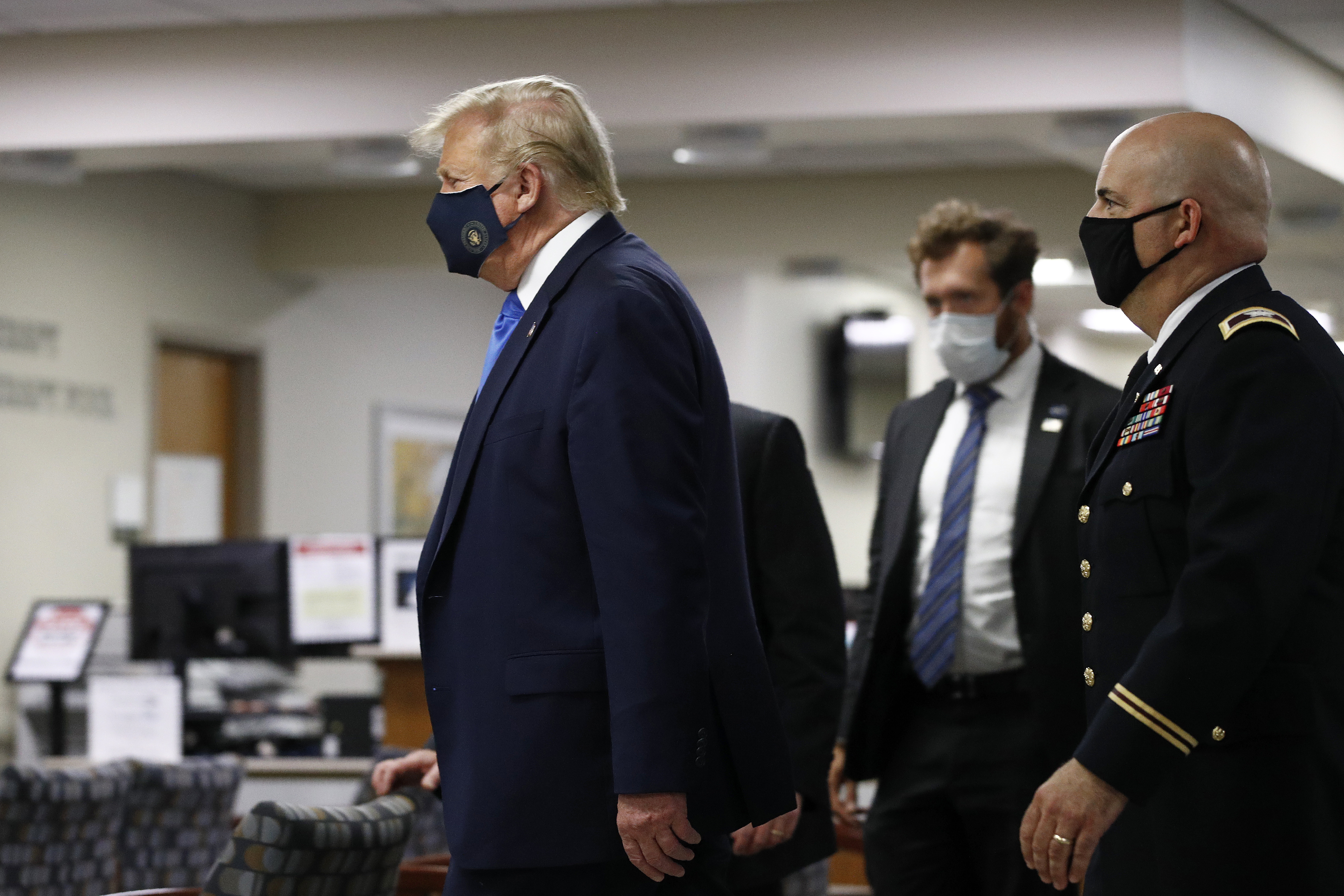 President Donald Trump wears a face mask as he walks down a hallway during a visit to Walter Reed National Military Medical Center in Bethesda, Md., on July 11, 2020.