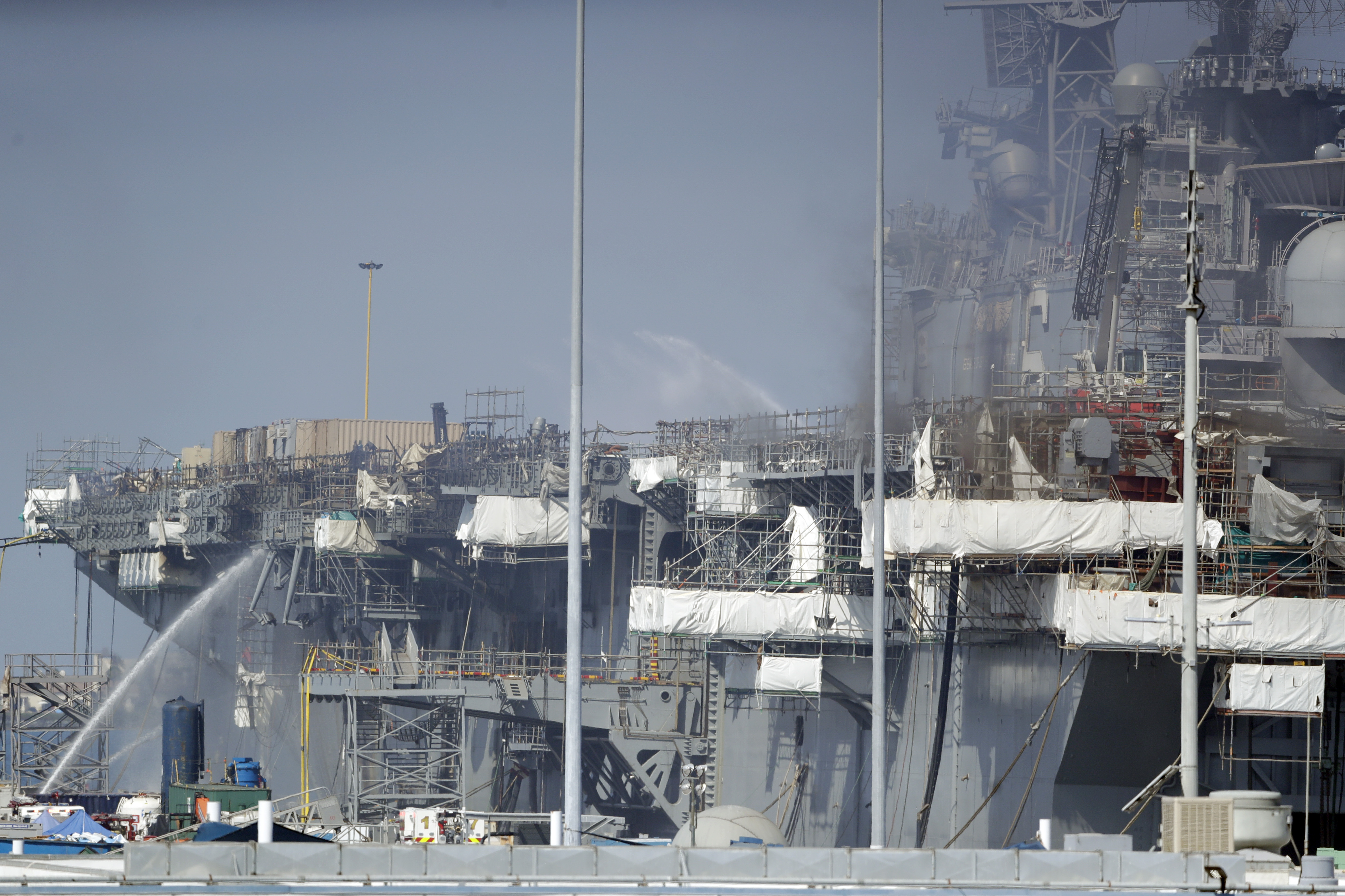 Fire crews spray water from the dock onto the side of the USS Bonhomme Richard, on July 14, 2020, in San Diego.