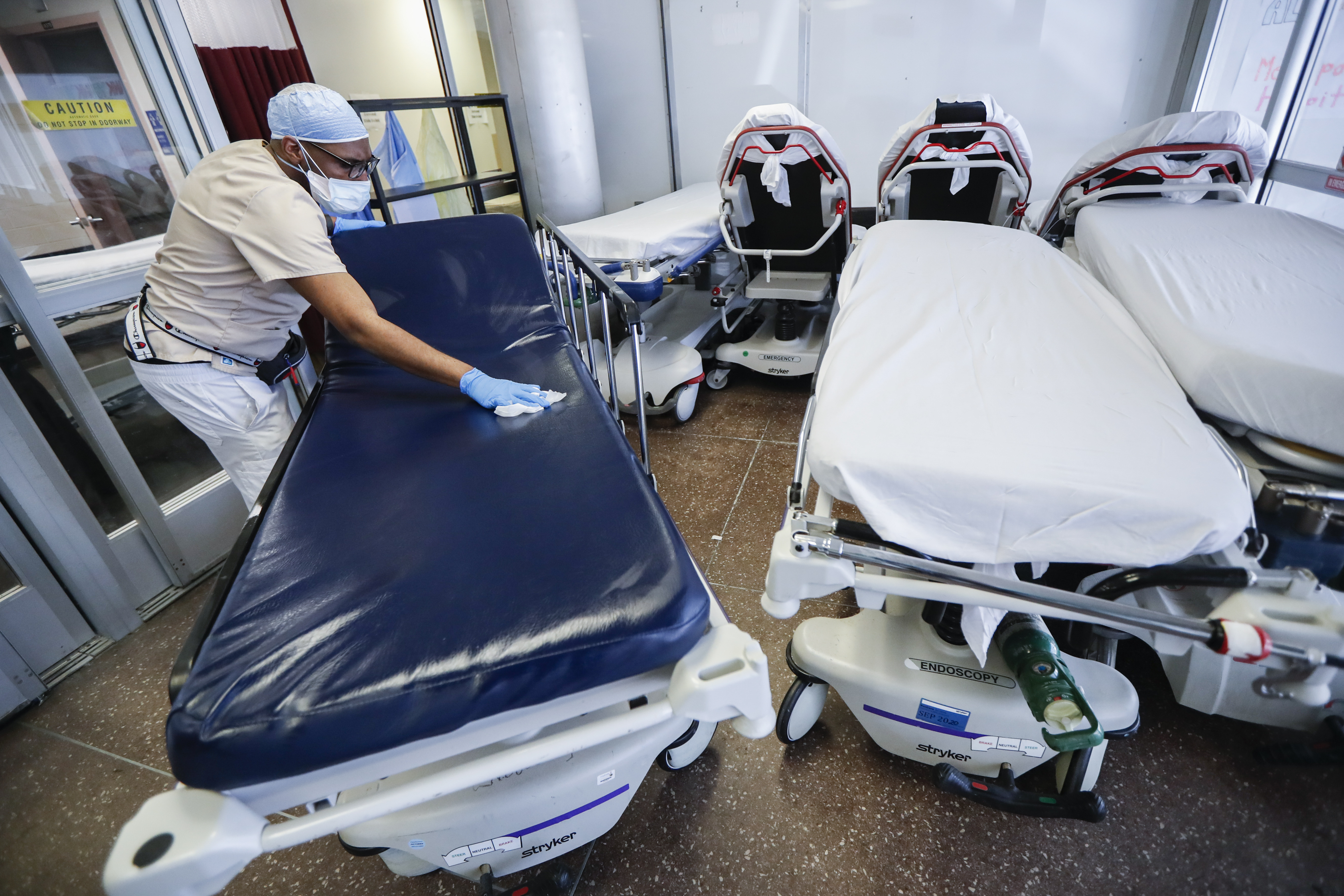 A medical worker wearing personal protective equipment cleans gurneys in the emergency department intake area in New York, on May 27, 2020.