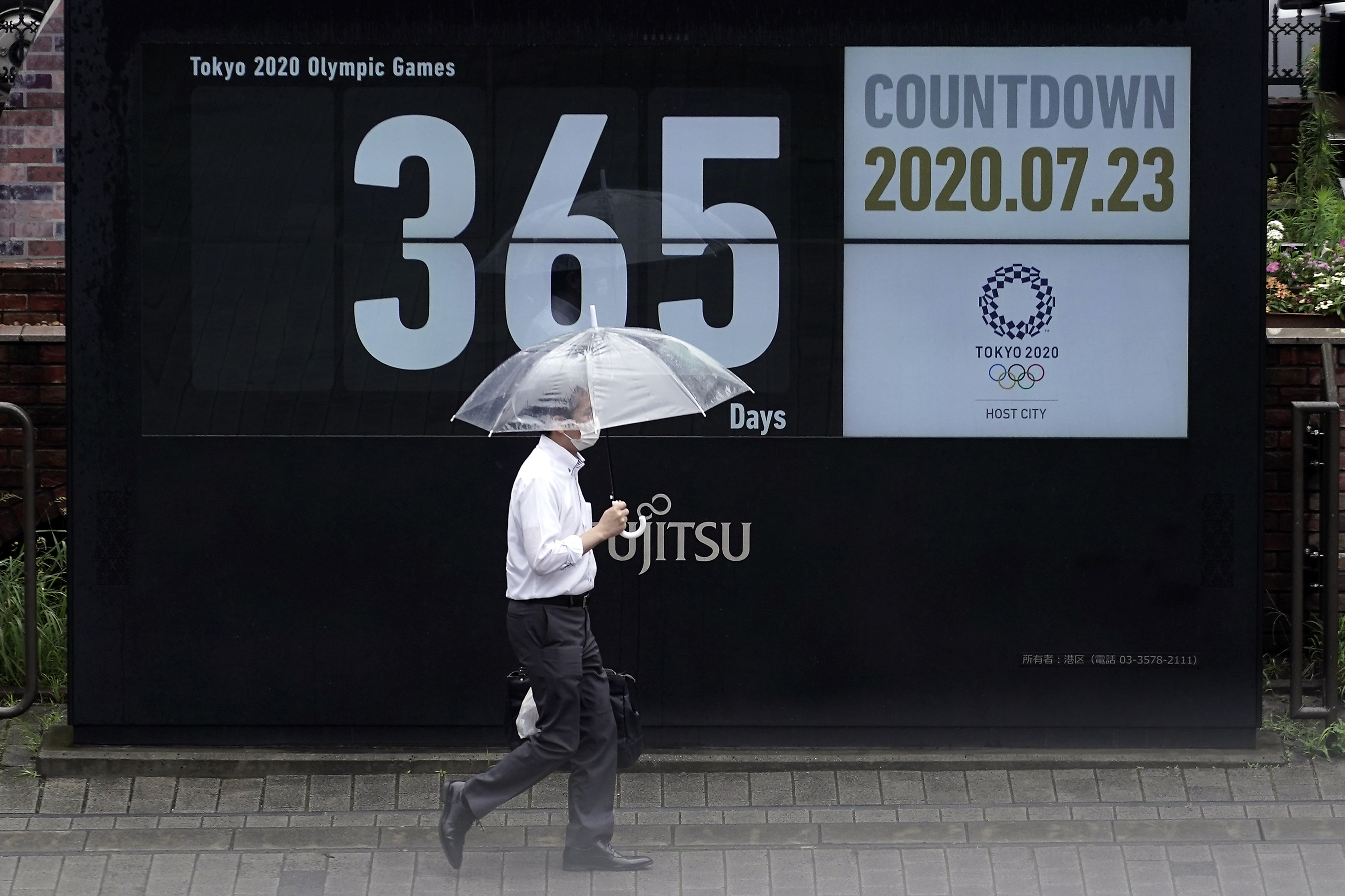 A man wearing a mask against the spread of the new coronavirus walks in front of a countdown calendar showing 356 day to start Tokyo 2020 Olympics Thursday, July 23, 2020, in Tokyo.
