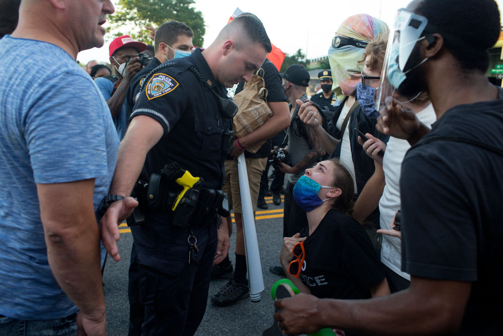 Black Lives Matter marchers plead with a police officer to arrest a right wing counter protestor who assaulted one of them outside of the 68th police precinct on July 12, 2020 in the Bay Ridge neighborhood of Brooklyn, New York.