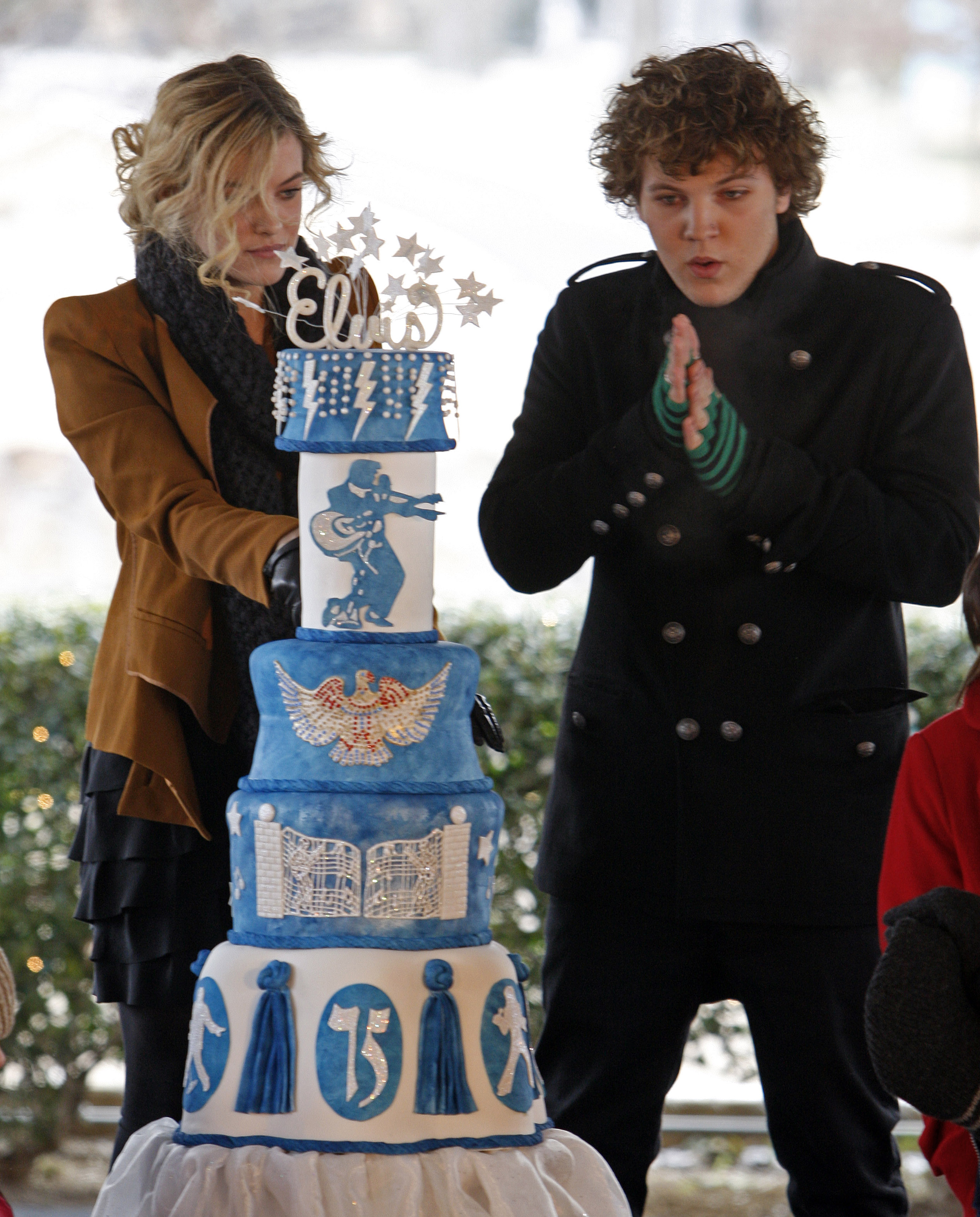 Riley Keough, 21, left, cuts the birthday cake as her brother, Benjamin, 18, right, warms his hands as they take part in a ceremony commemorating Elvis Presley's 75th birthday on Friday, Jan. 8, 2010 in Memphis, Tenn. Both are the children of Lisa Marie Presley and the grandchildren of Elvis Presley.