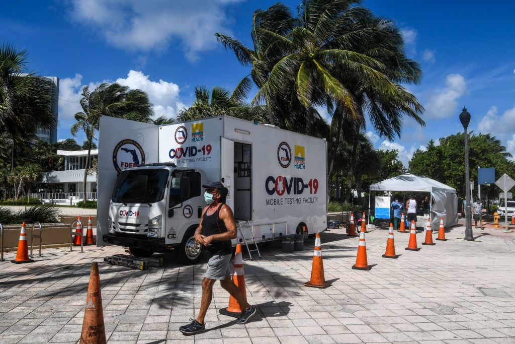 A man walks past the Aardvark Mobile Health's Mobile Covid-19 Testing Truck in Miami Beach, on July 24.