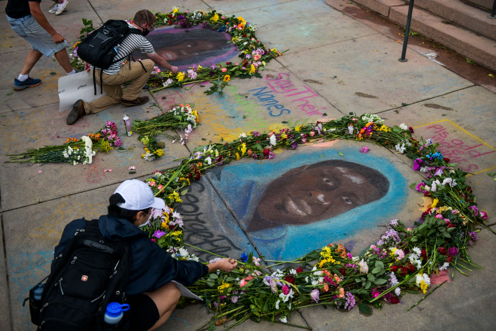 People place flowers around chalk portraits of George Floyd and Breonna Taylor on the steps of the Colorado State Capitol as people protest their deaths on June 6, 2020 in Denver, Colo.