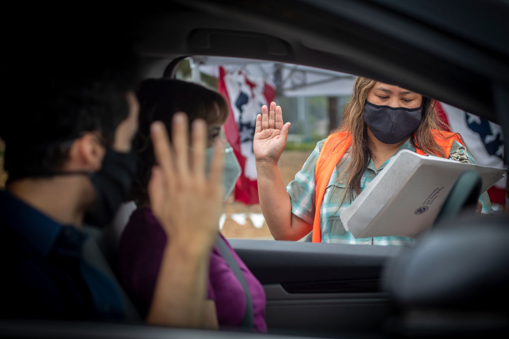 U.S. Citizenship and Immigration Services officer Rochelle Reyes, right, administers the oath of allegiance to Brian Gebel, left, during a drive through citizenship naturalization in Laguna Niguel, California, on June 23, 2020.