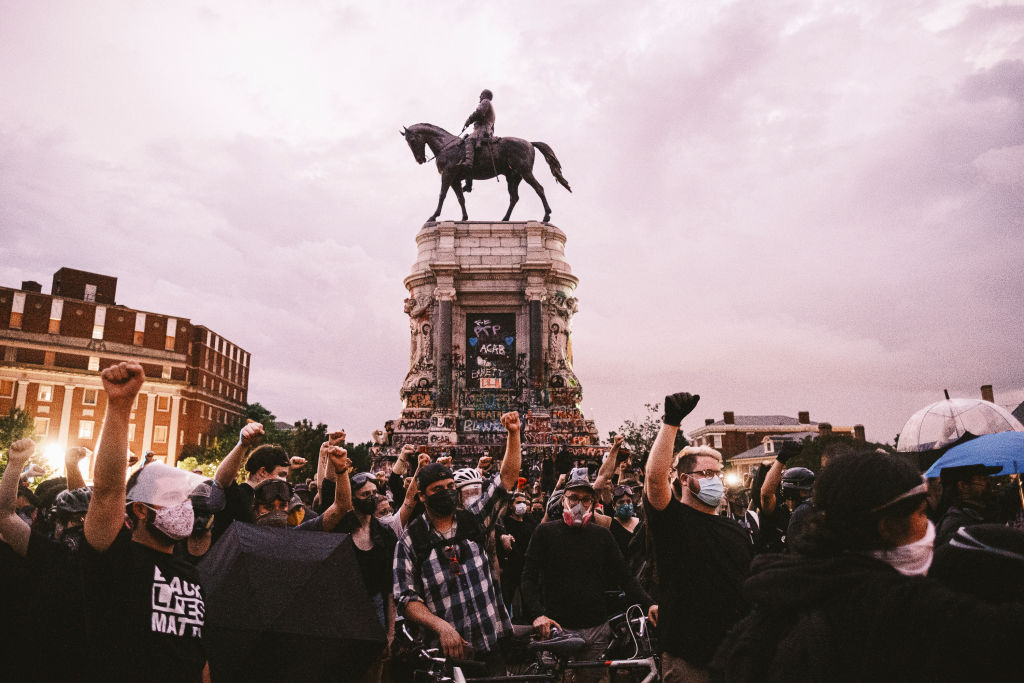 Protesters raise their fists in the air in front of Richmond, Va.'s, Robert E. Lee statue on June 23.