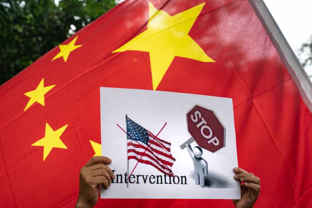Pro-Beijing supporters hold China national flags and placards as they take part in a rally outside of Consulate General of the United States in Hong Kong on June 26, 2020.