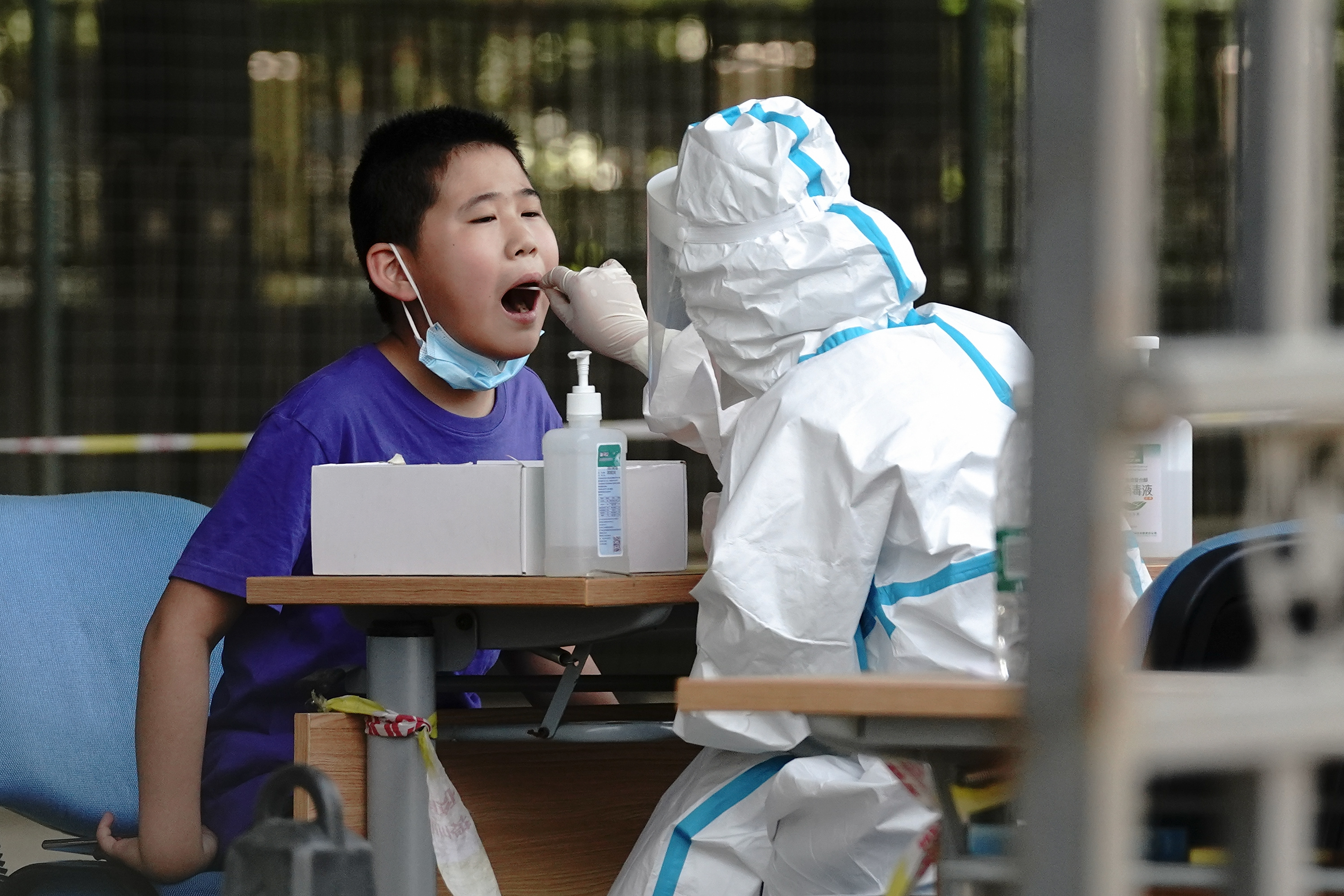 A medical worker wearing a protective suit takes a swap at a temporary COVID-19 testing site on June 30, 2020 in Beijing, China.