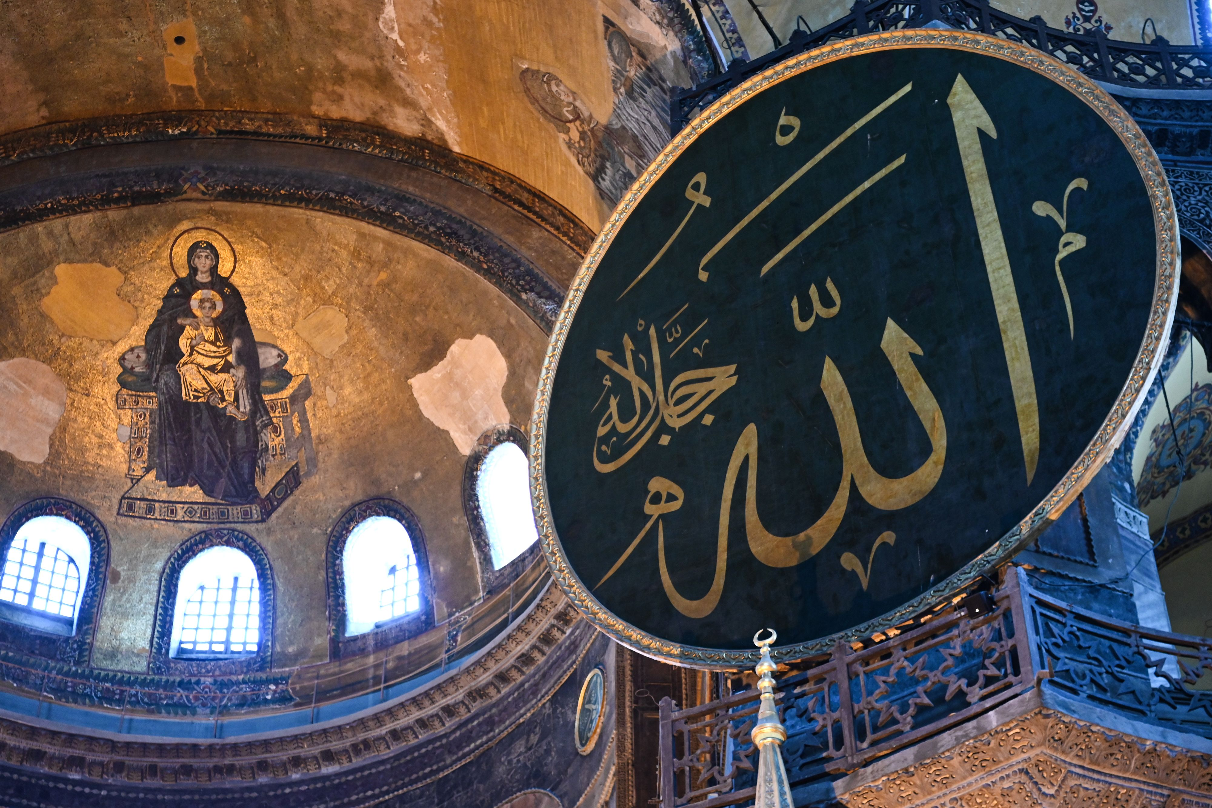 This picture taken on July 2, 2020 shows the Virgin Mary and child fresco (L) and a calligraphic Roundel with Arabic letters bearing the name of Allah and other Muslim prophets hanging on the dome of the Hagia Sophia museum, in Istanbul, Turkey.