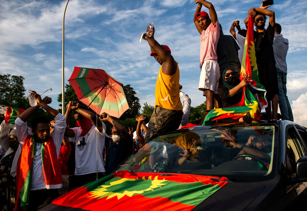 Demonstrators hold up a crossed-arms gesture during a protest after the death of musician and activist Hachalu Hundessa on the westbound lane of Interstate 94 on July 1, 2020 in St Paul, Minnesota. Hundessa was shot and killed in Addis Ababa, Ethiopia on June 29, which has sparked ongoing protests across the globe.