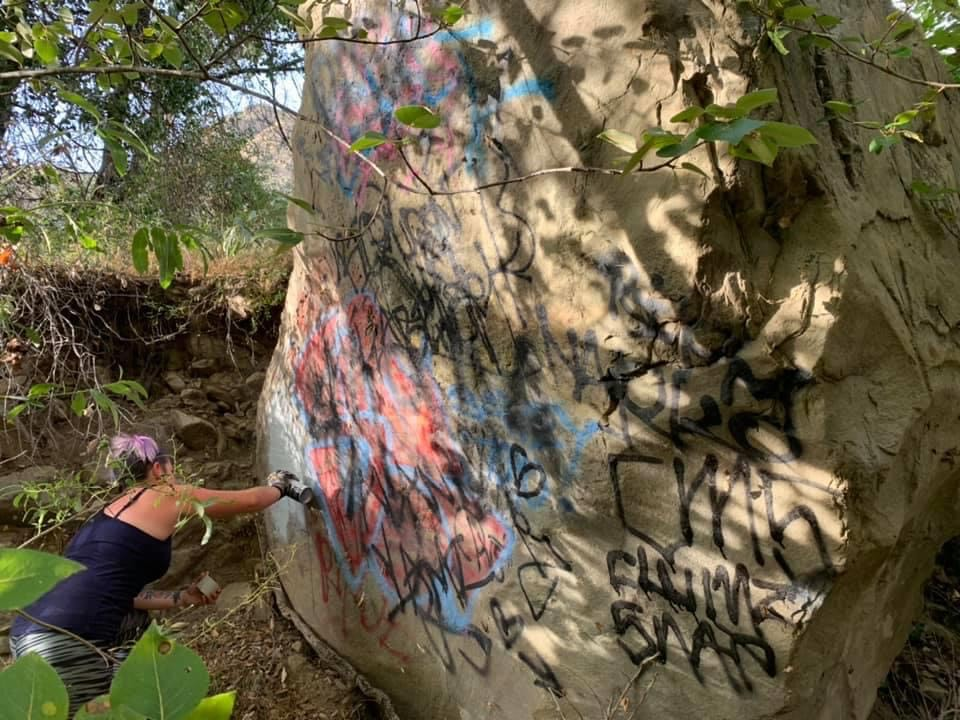 A volunteer works to remove graffiti from the Santa Paula Canyon in Ventura County, Calif.