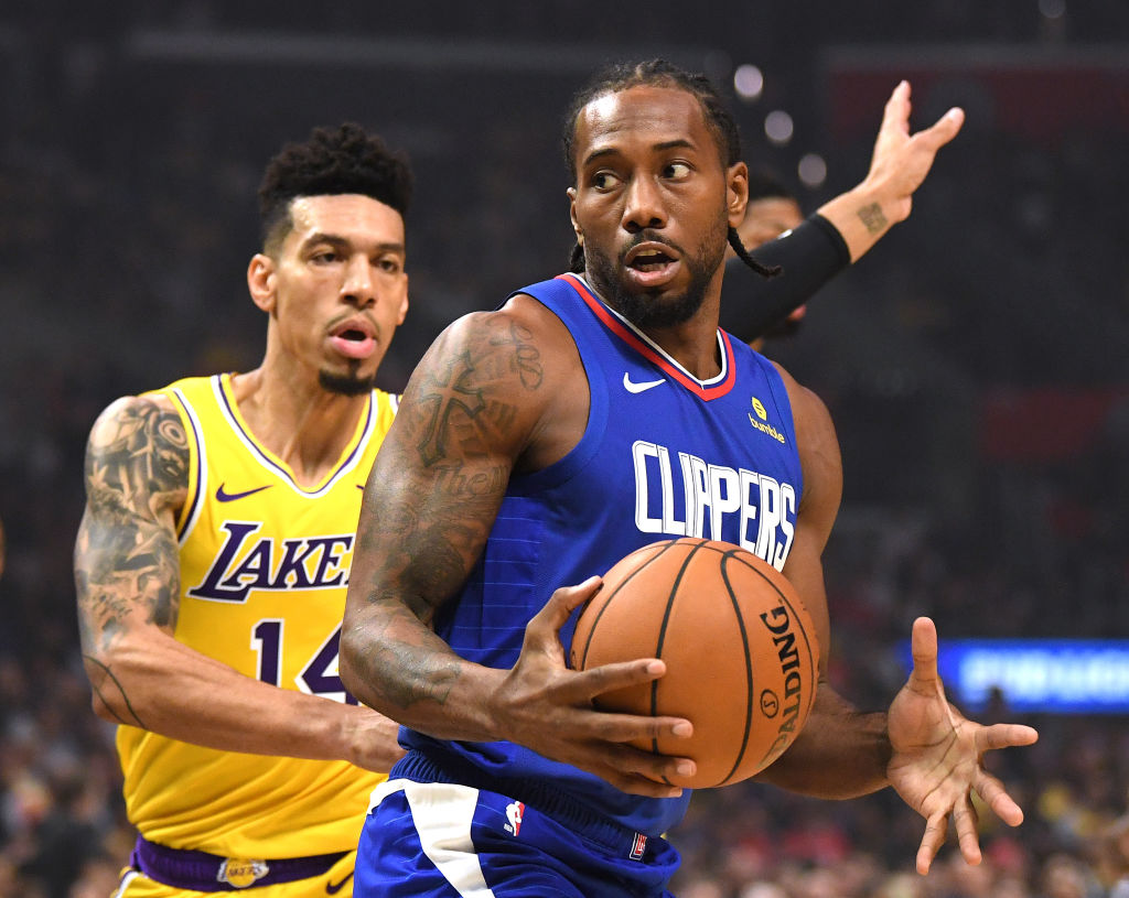 Kawhi Leonard #2 of the LA Clippers spins for a shot in front of Danny Green #14 of the Los Angeles Lakers during a 112-102 Clipper win in the LA Clippers season home opener at Staples Center on October 22, 2019 in Los Angeles, California.