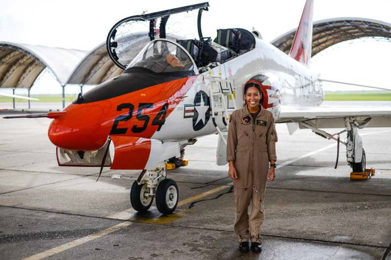 Student Naval Aviator Lt. j.g. Madeline Swegle, assigned to the Redhawks of Training Squadron (VT) 21 stands by a T-45C Goshawk training aircraft following her final flight to complete the undergraduate Tactical Air (Strike) pilot training syllabus, at Naval Air Station Kingsville, Texas, on July 7, 2020.