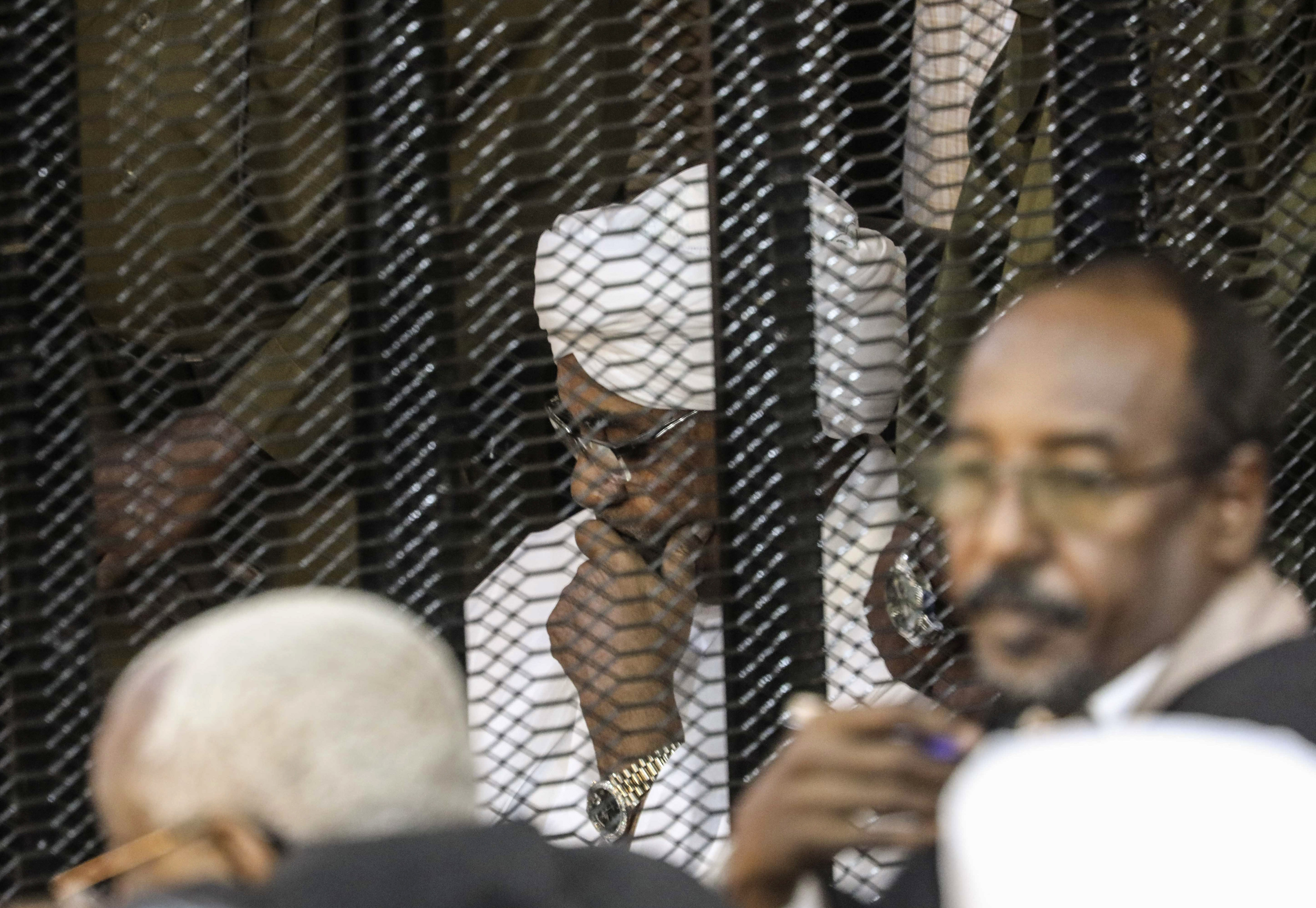 In this Aug. 24, 2019 file photo, Sudan's autocratic former President Omar al-Bashir sits in a cage during his trial on corruption and money laundering charges, in Khartoum, Sudan. On Tuesday, July 21, 2020, al-Bashir is back in court, this time facing charges of plotting the 1989 Islamist-backed coup that removed an elected government and brought him to power. The trial adjourned until Aug. 11.