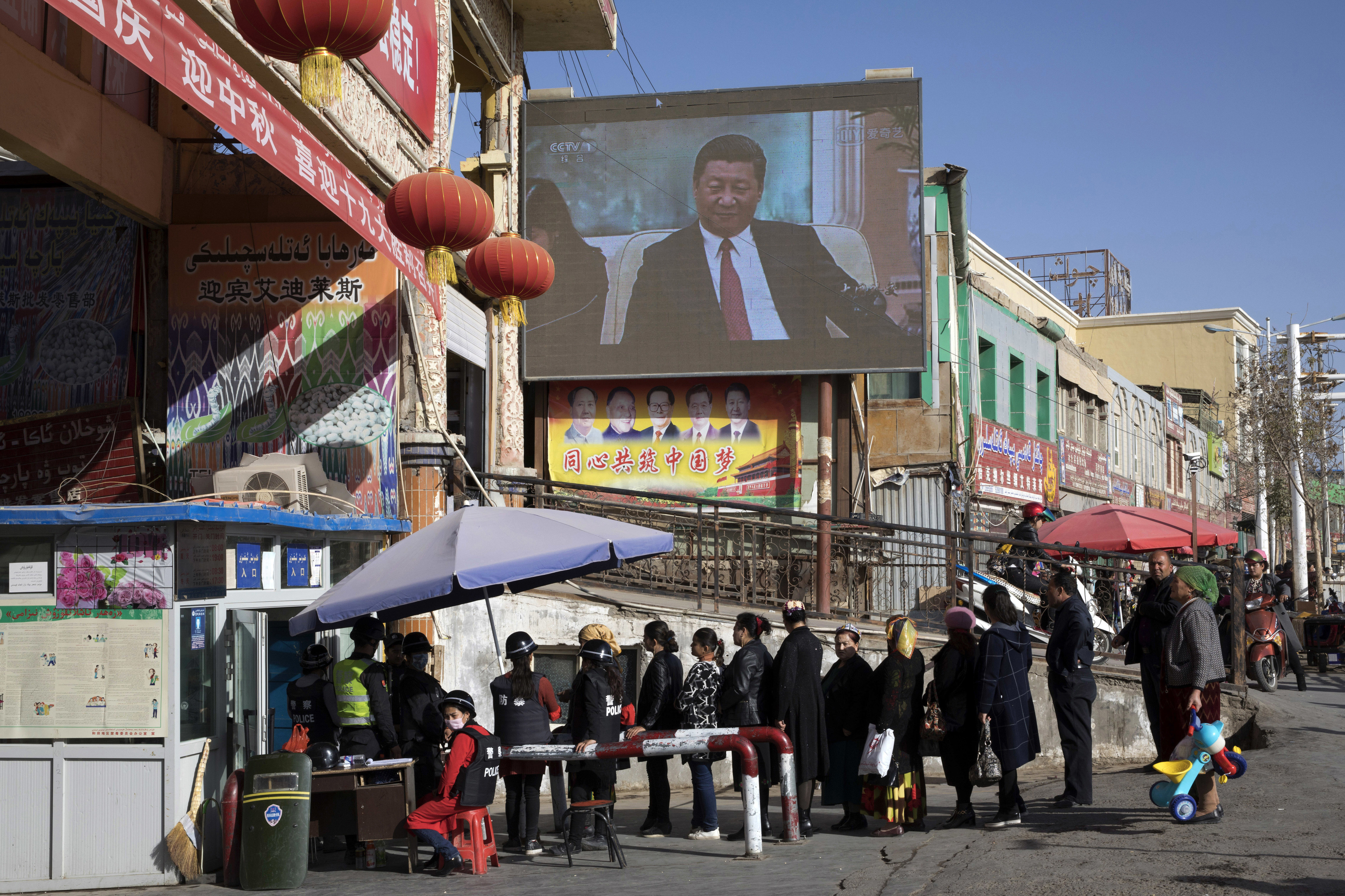 In this Nov. 3, 2017, file photo, residents walk through a security checkpoint into the Hotan Bazaar where a screen shows Chinese President Xi Jinping in Hotan in western China's Xinjiang region. China says the U.N.'s counterterrorism chief visited Xinjiang last week despite protests from the U.S. and a rights group that the trip would be inappropriate in light of the human rights conditions in the far west region.