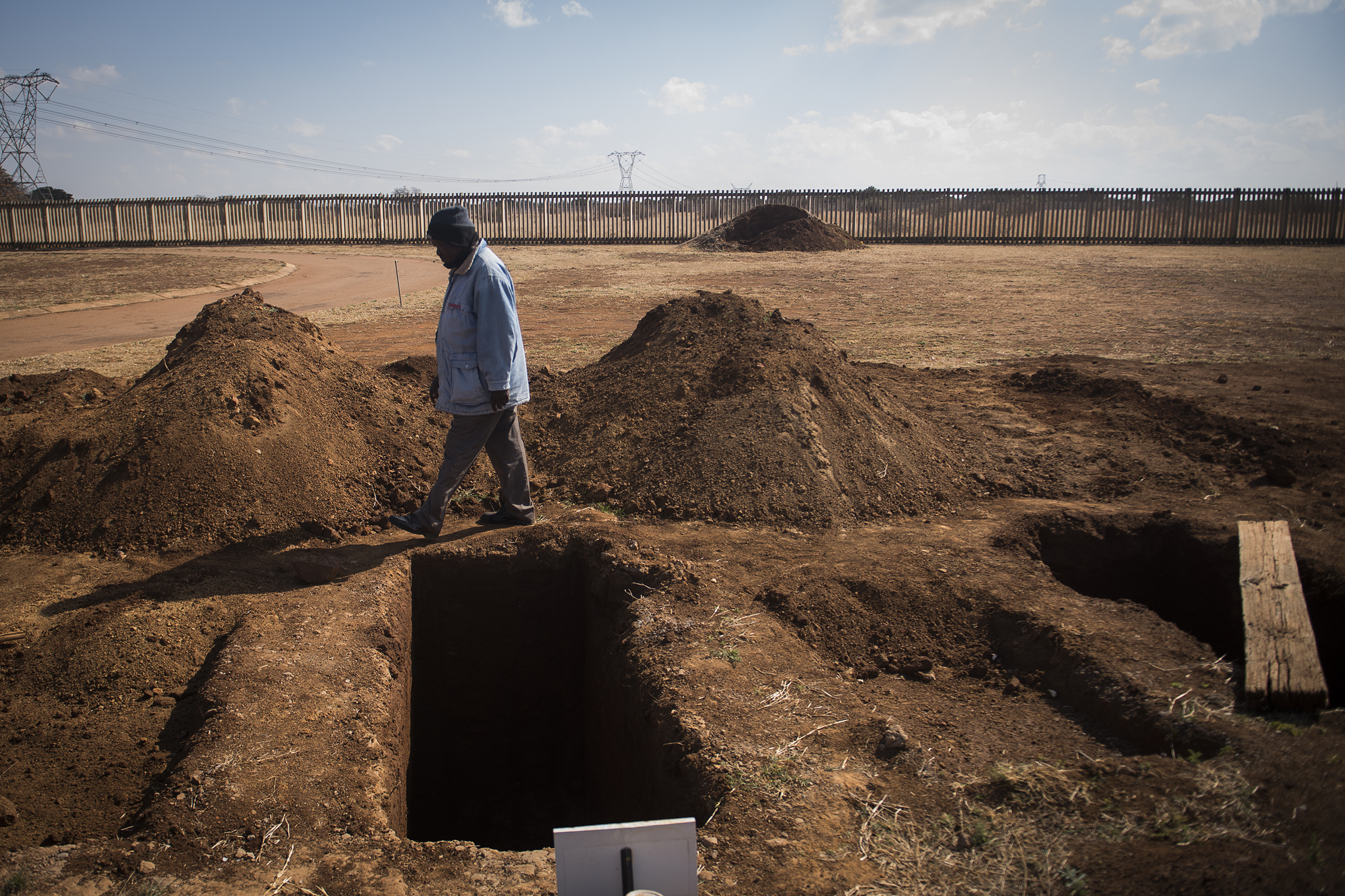 A worker walks past a freshly-dug graves at the Honingnestkrans Cemetery, North of Pretoria, South Africa, July 9, 2020.