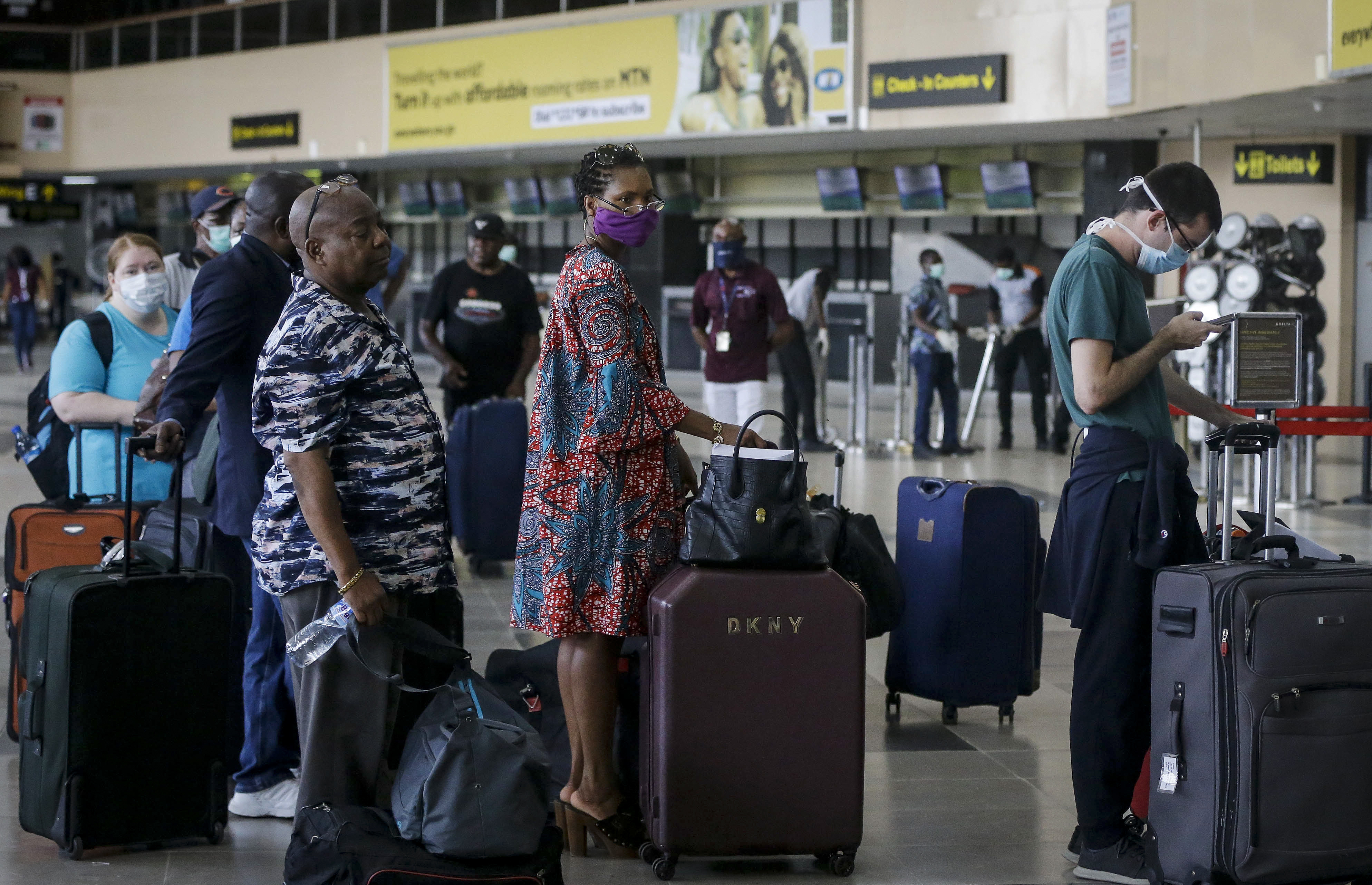 In this Tuesday, April 7, 2020 file photo, U.S. citizens queue to check in and be repatriated aboard an evacuation flight arranged by the U.S. embassy and chartered with Delta Air Lines, at the Murtala Mohammed International Airport in Lagos, Nigeria.