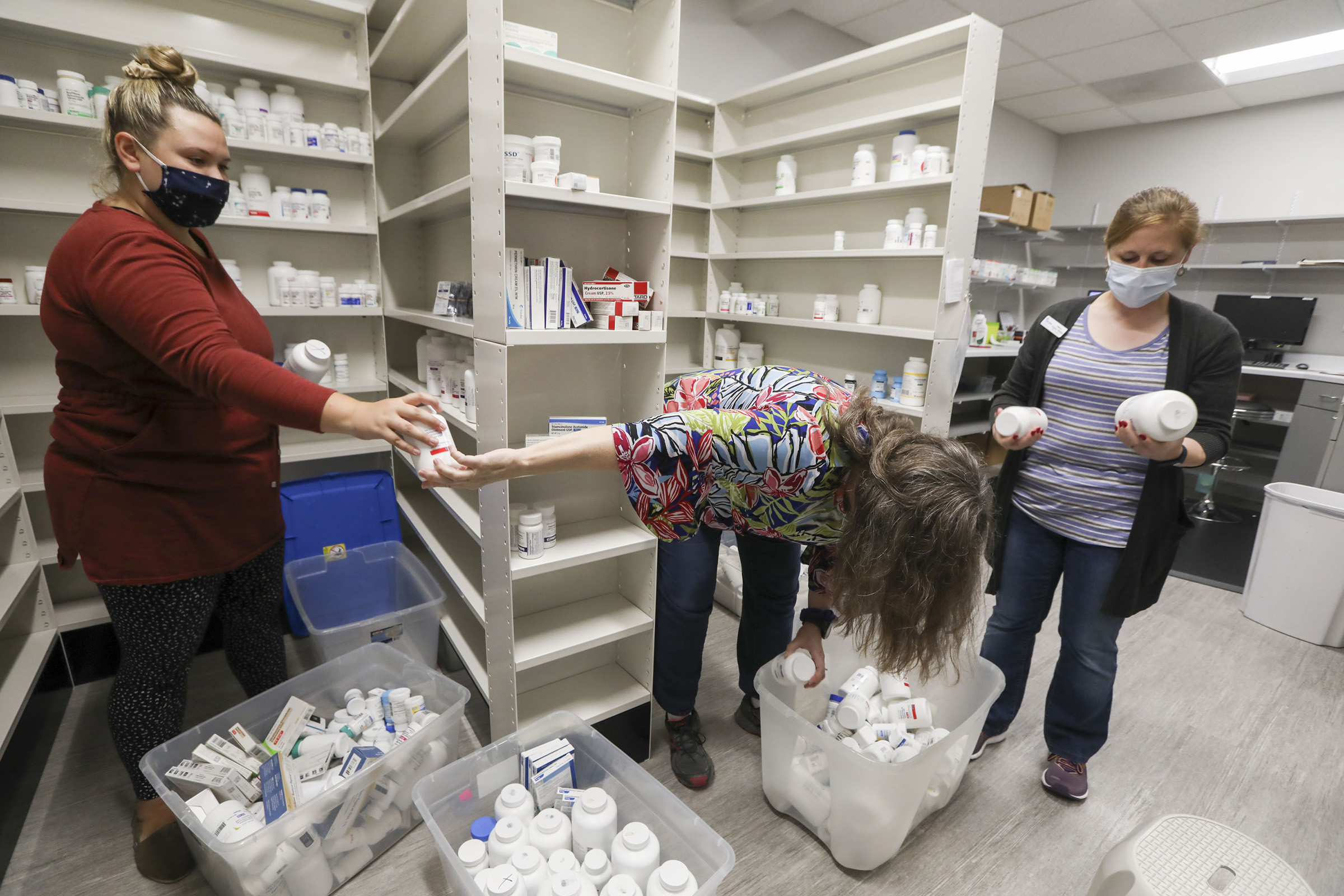 Faith Crawley, left, an AmeriCorps Vista worker, Margie Leonard, center, assistant clinic coordinator, and Mallory Hughes, clinic coordinator, stock the new medicine room at the new His Hands Free Clinic in Cedar Rapids on July 1, 2020.