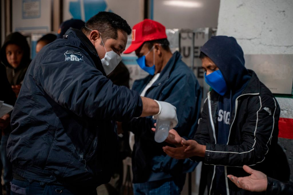 A Chihuahua State police officer gives out hand sanitizer to migrants at the Paso del Norte International Bridge in Ciudad Juarez, Mexico on April 6, 2020. As immigration courts have been closed due to the pandemic, people seeking asylum under the  Remain in Mexico  policy are still expected to show up in the dangerous city center before dawn to receive new dates despite stay-at-home order on both sides of the border.