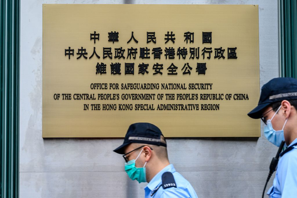 Police walk past a plaque outside the Office for Safeguarding National Security of the Central People's Government in Hong Kong after its official inauguration on July 8, 2020.